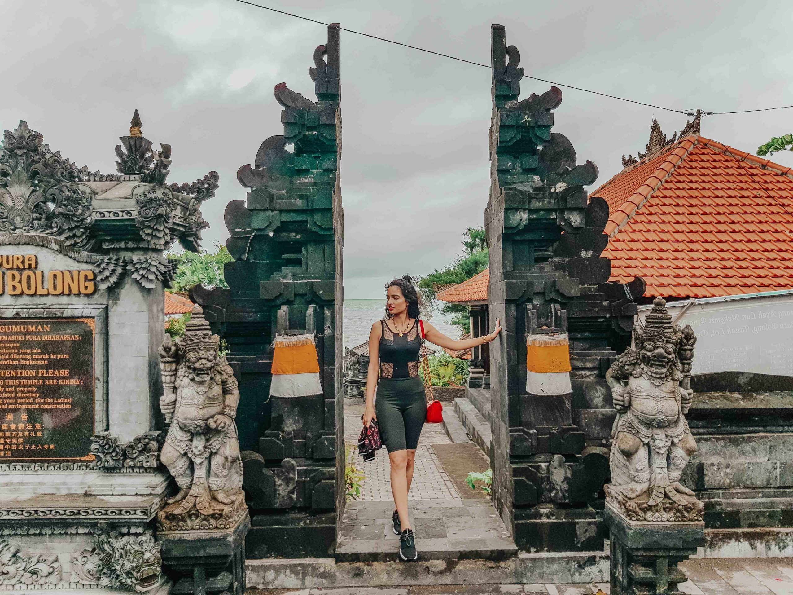 girl fashion blogger standing at the gates of Tanah Lot in Bali, for the blog about travel-guide and travel-tips to Bali, Indonesia for first-timers