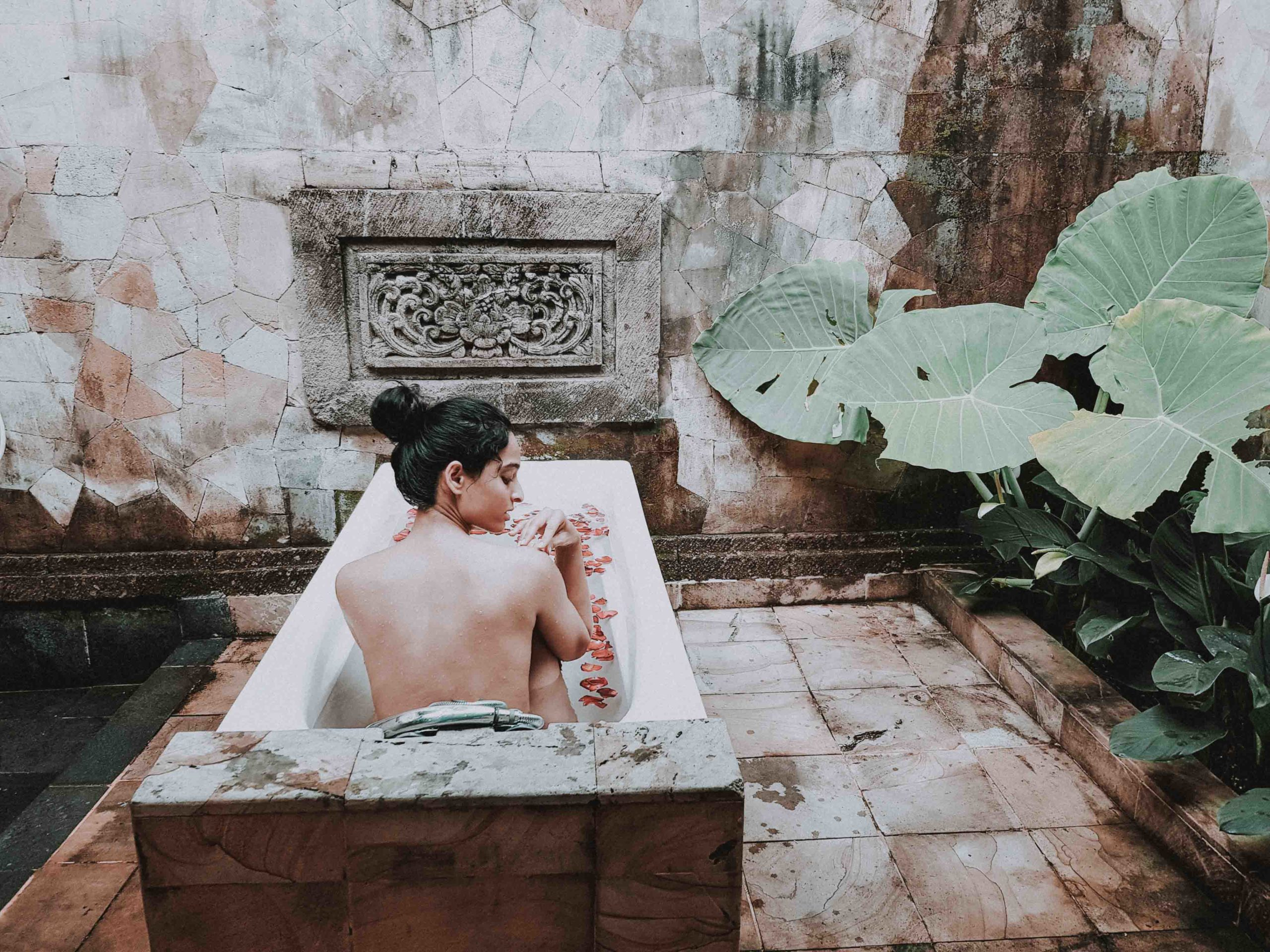 girl fashion blogger sitting in an outdoor bathtub at the spa in Bali for the blog about travel-guide and travel-tips to Bali, Indonesia for first-timers