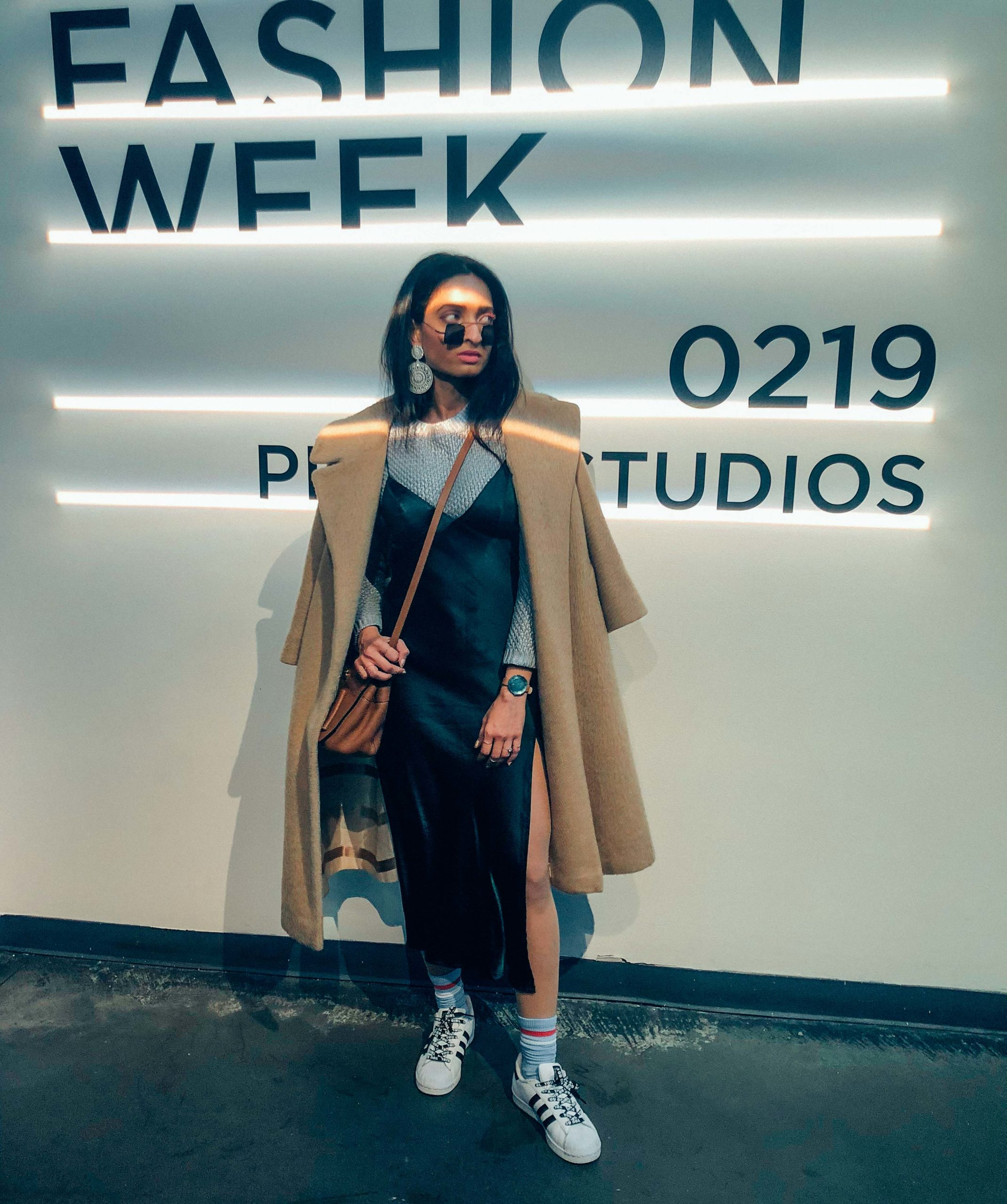 girl in green camisole dress and nude coat with sneakers standing in front of fashion week sign