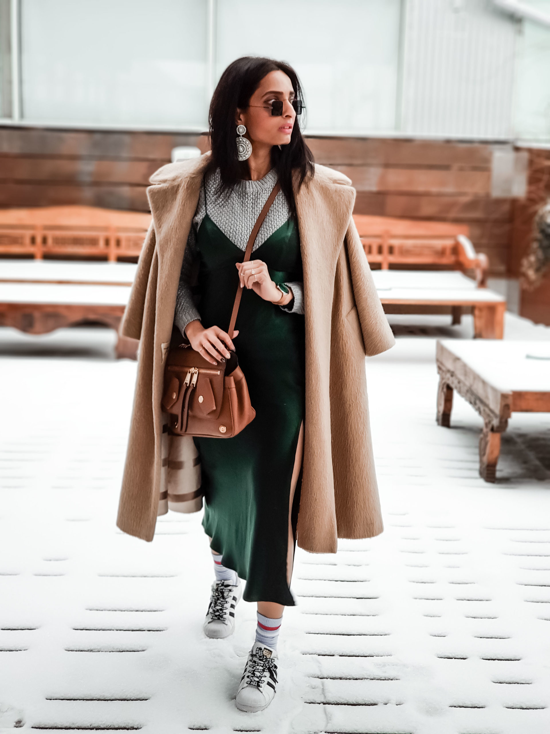 girl fashion blogger wearing green satin camisole dress with sneakers and blue socks and nude coloured coat outfit for streetstyle at new york fashion week 2019