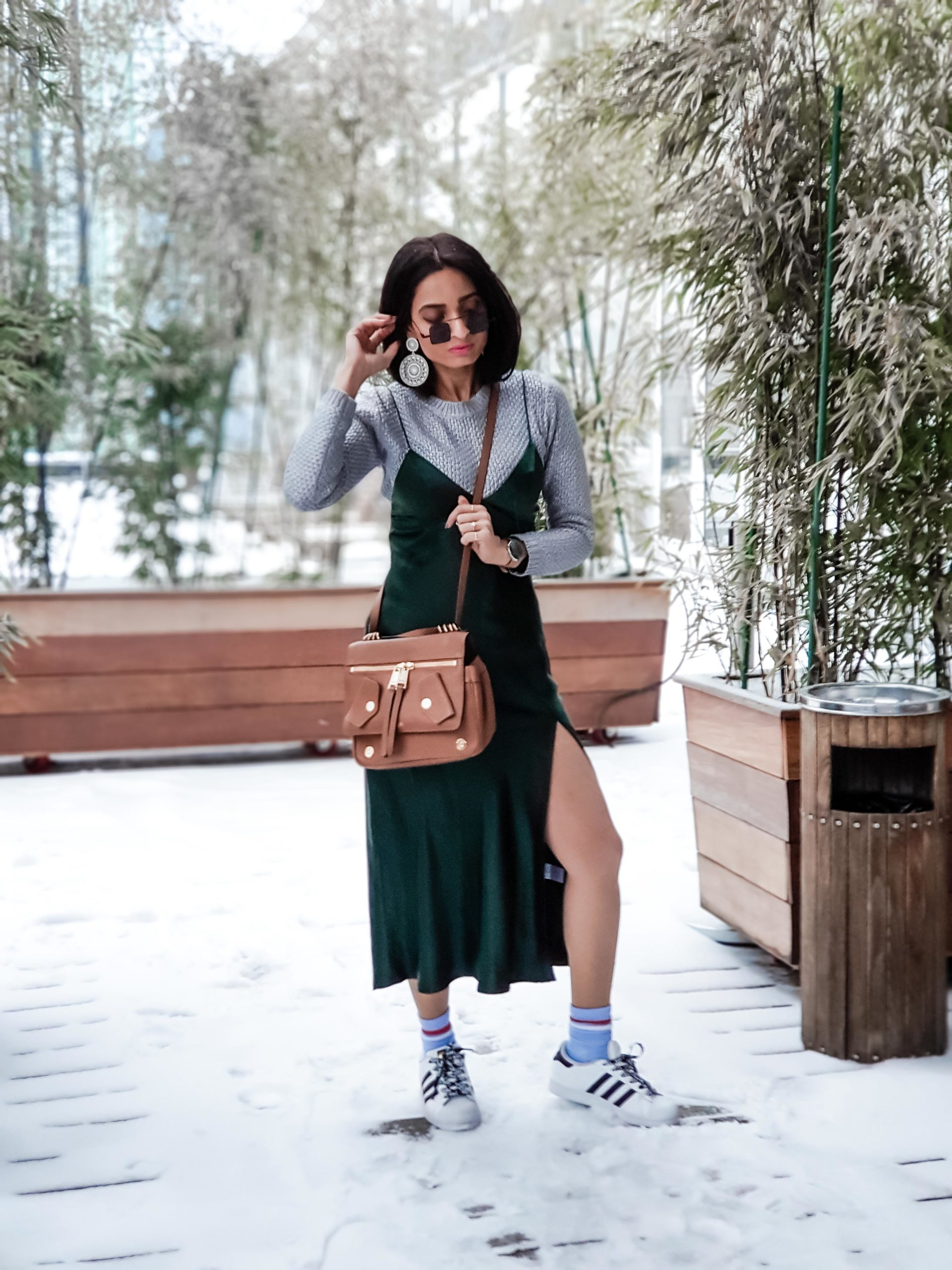 girl fashion blogger wearing green satin camisole dress with sneakers and blue socks and tan purse outfit for streetstyle at new york fashion week 2019