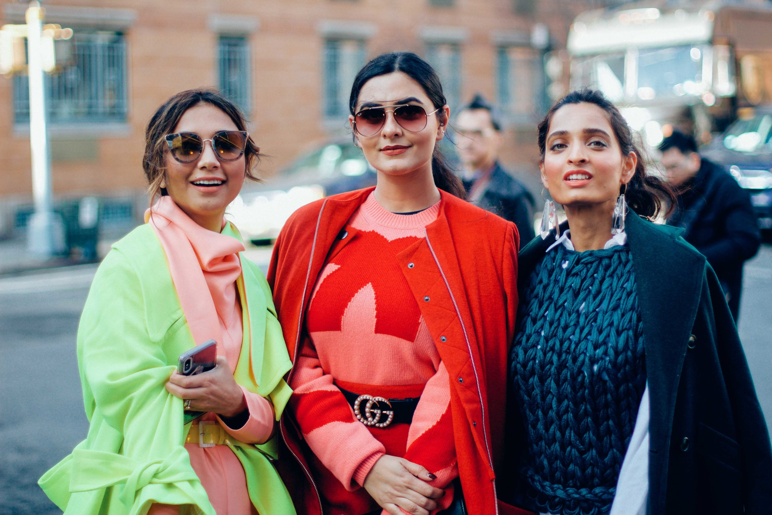3 girls wearing colour block outfits for fashion week in shades of red and green