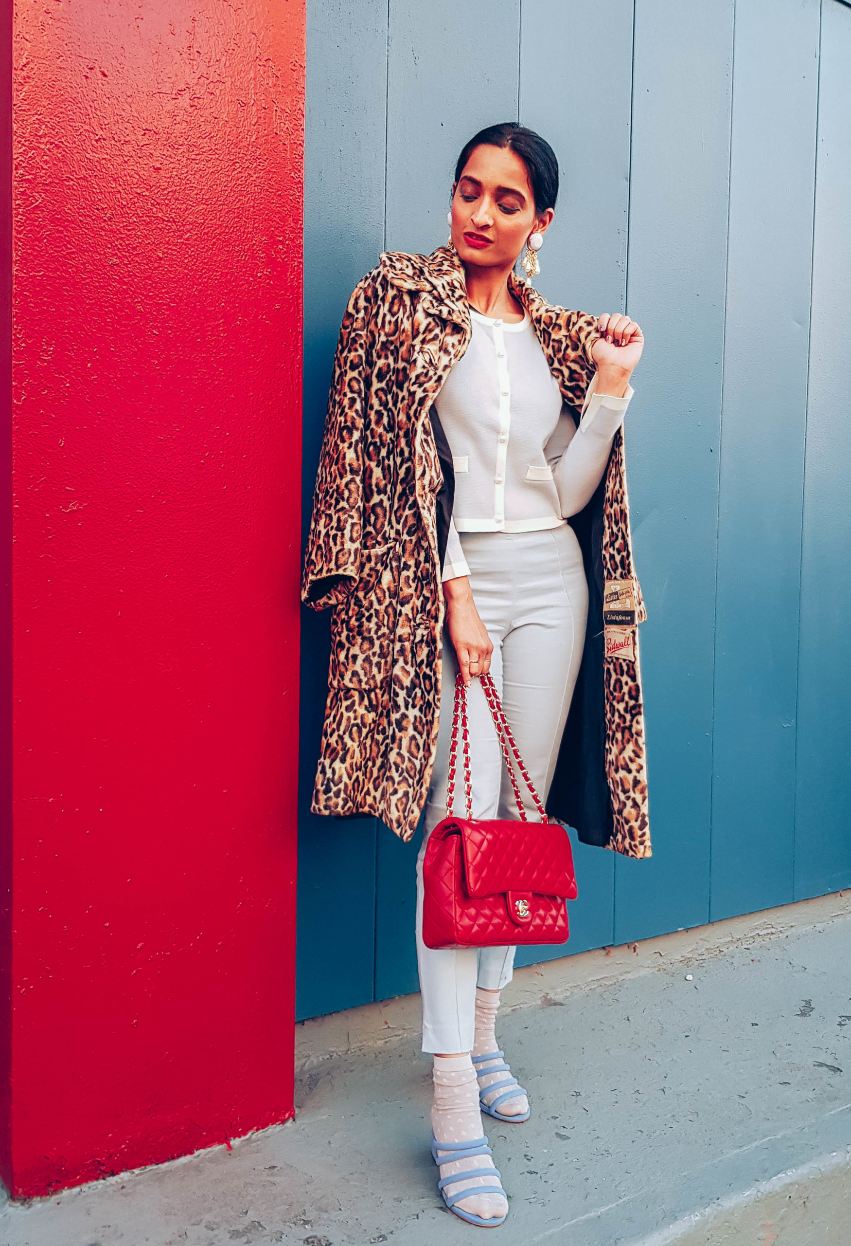 girl fashion blogger wearing pale blue monochromatic outfit with red vintage chanel purse and leopard print coat
