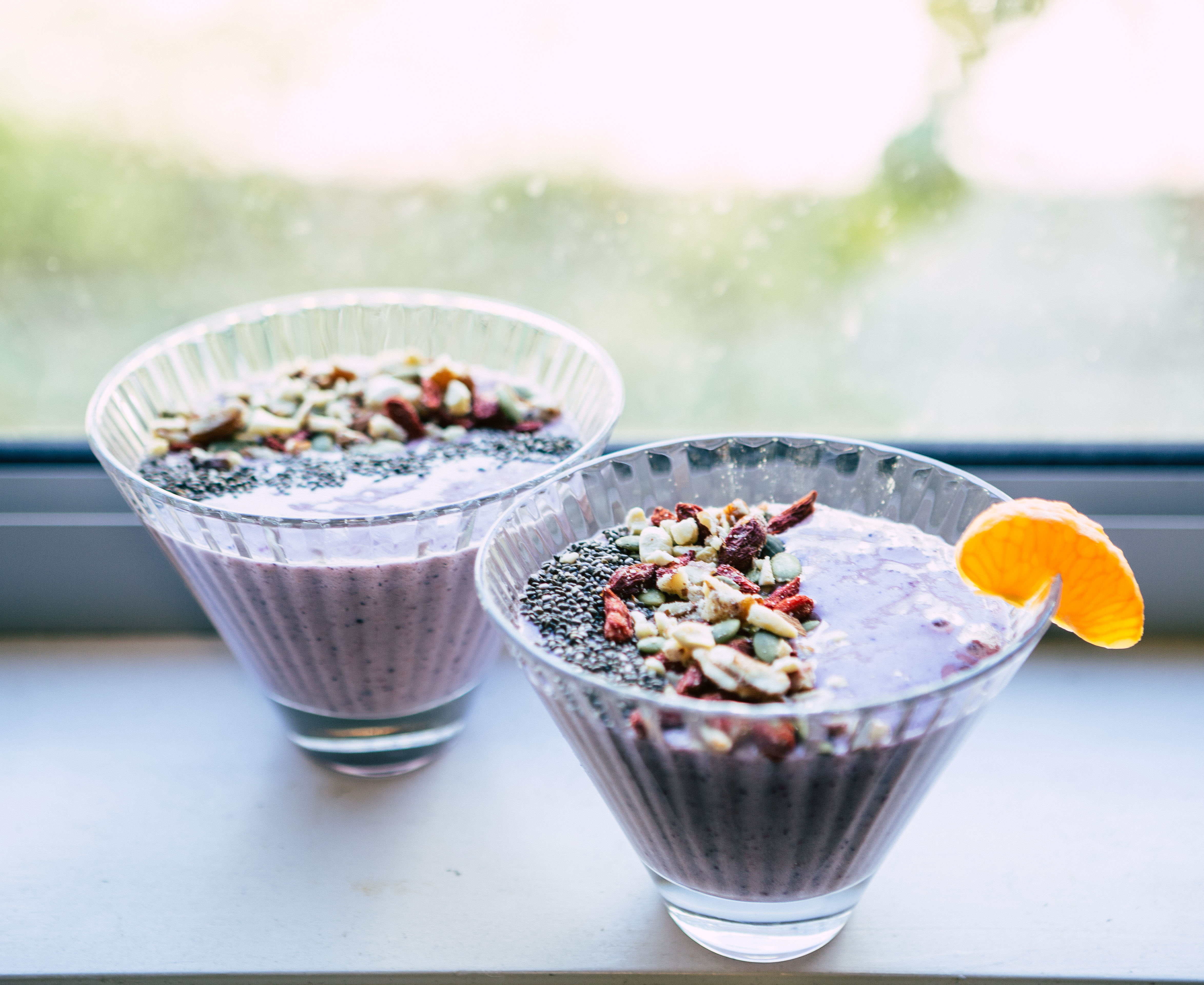 smoothie in ice cream cups topped with nuts and chia seeds