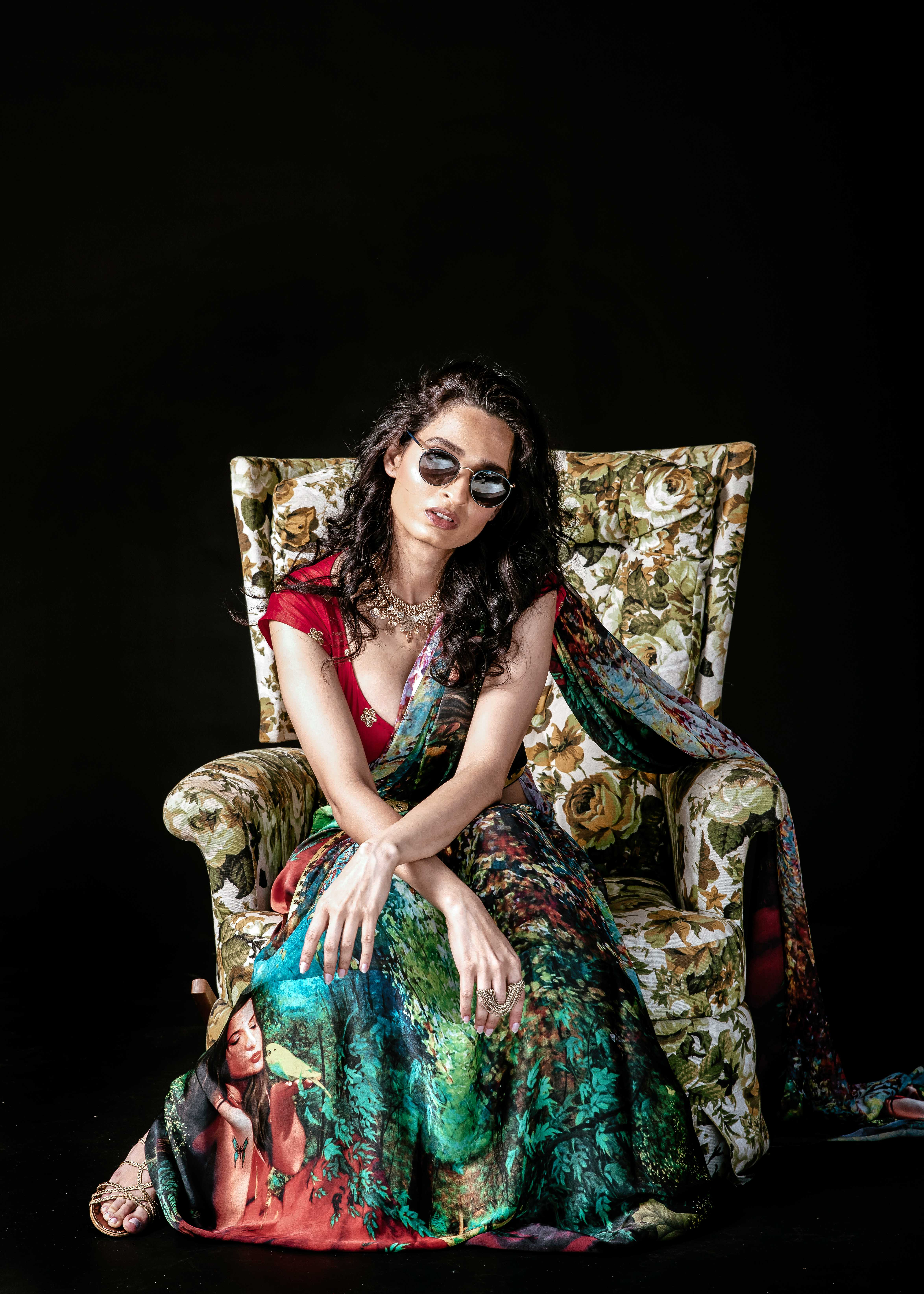 green saree with red blouse and yellow off-white belt sitting on floral chair indian outfit style wearing sunglasses