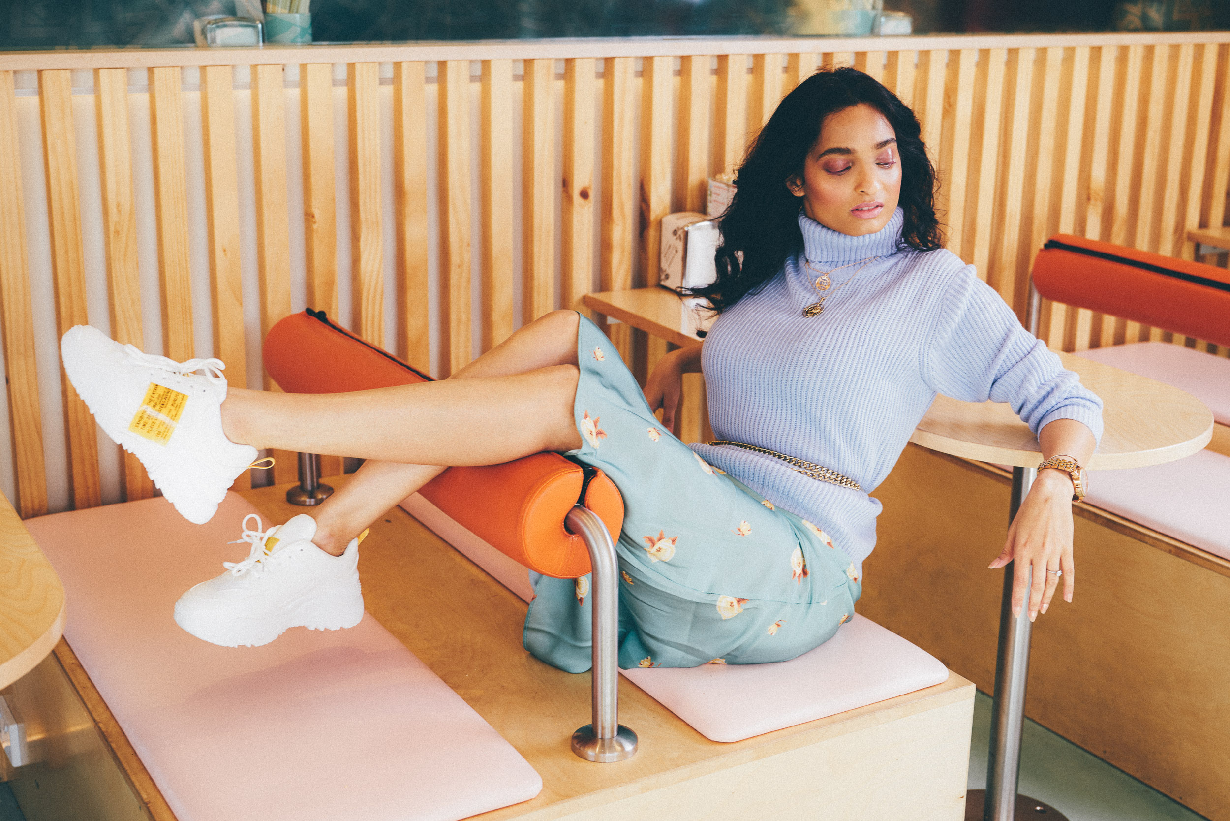 Girl sitting in restaurant with pastel interiors, wearing mint green dress and lavender sweater with chunky white sneakers outfit. Illustrative image for to discuss what i wish my younger self knew