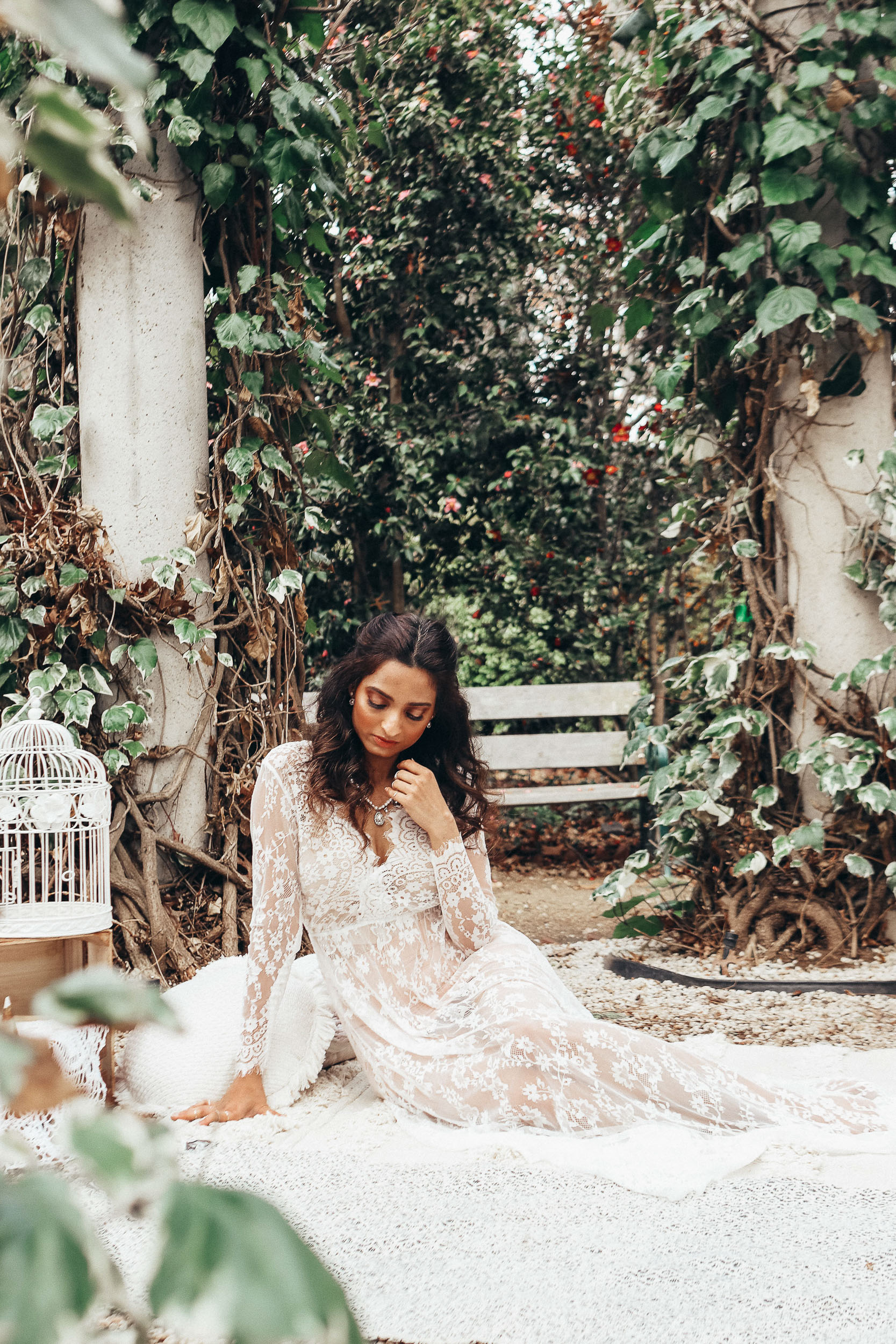 Girl sitting on a mat in forest wearing white lace gown, moody shot-to discuss PMS and mental health