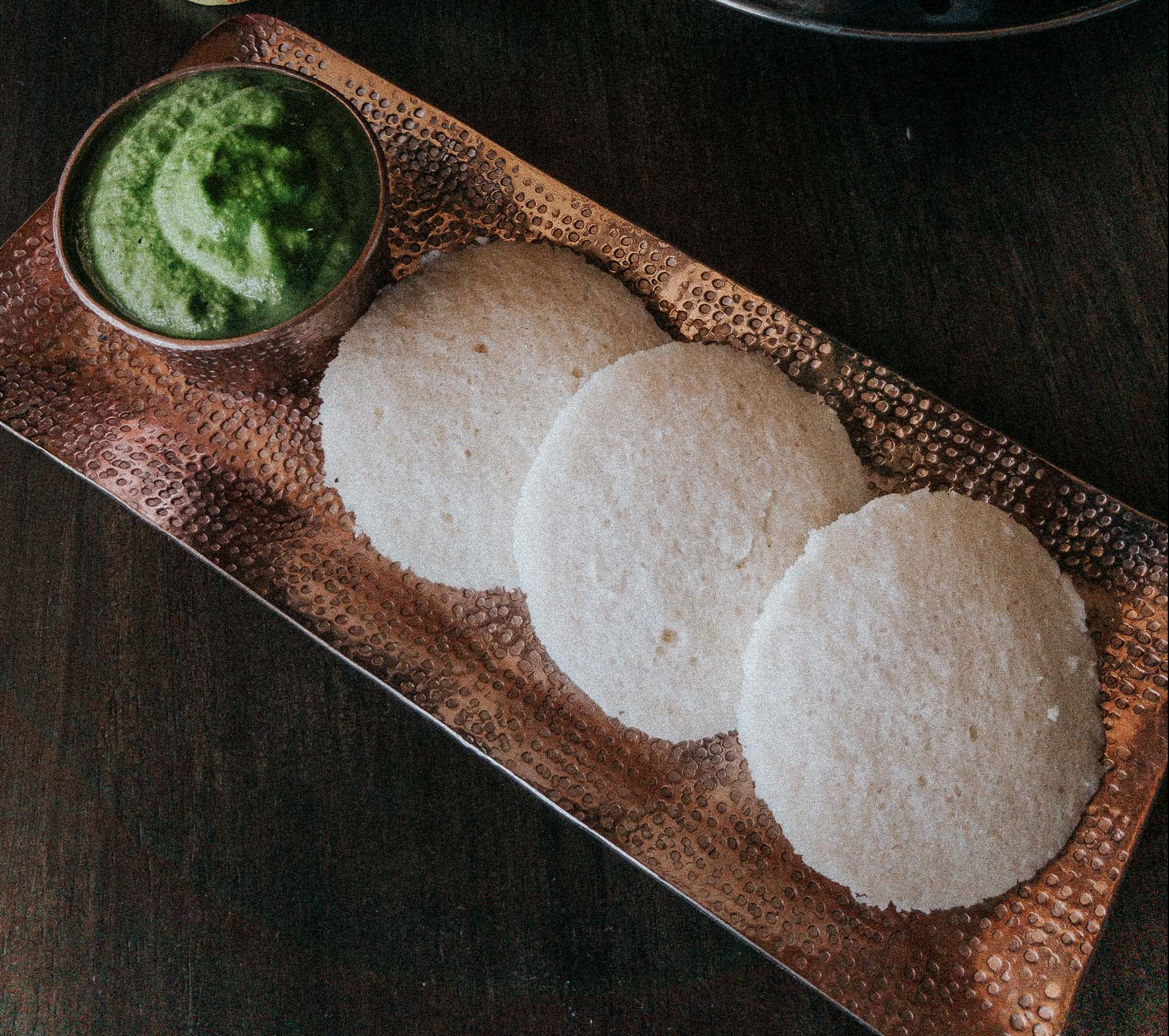 Flatlay of idli with green peanut coconut coriander chutney alongside an idli stand and kathakali dancer boblehead