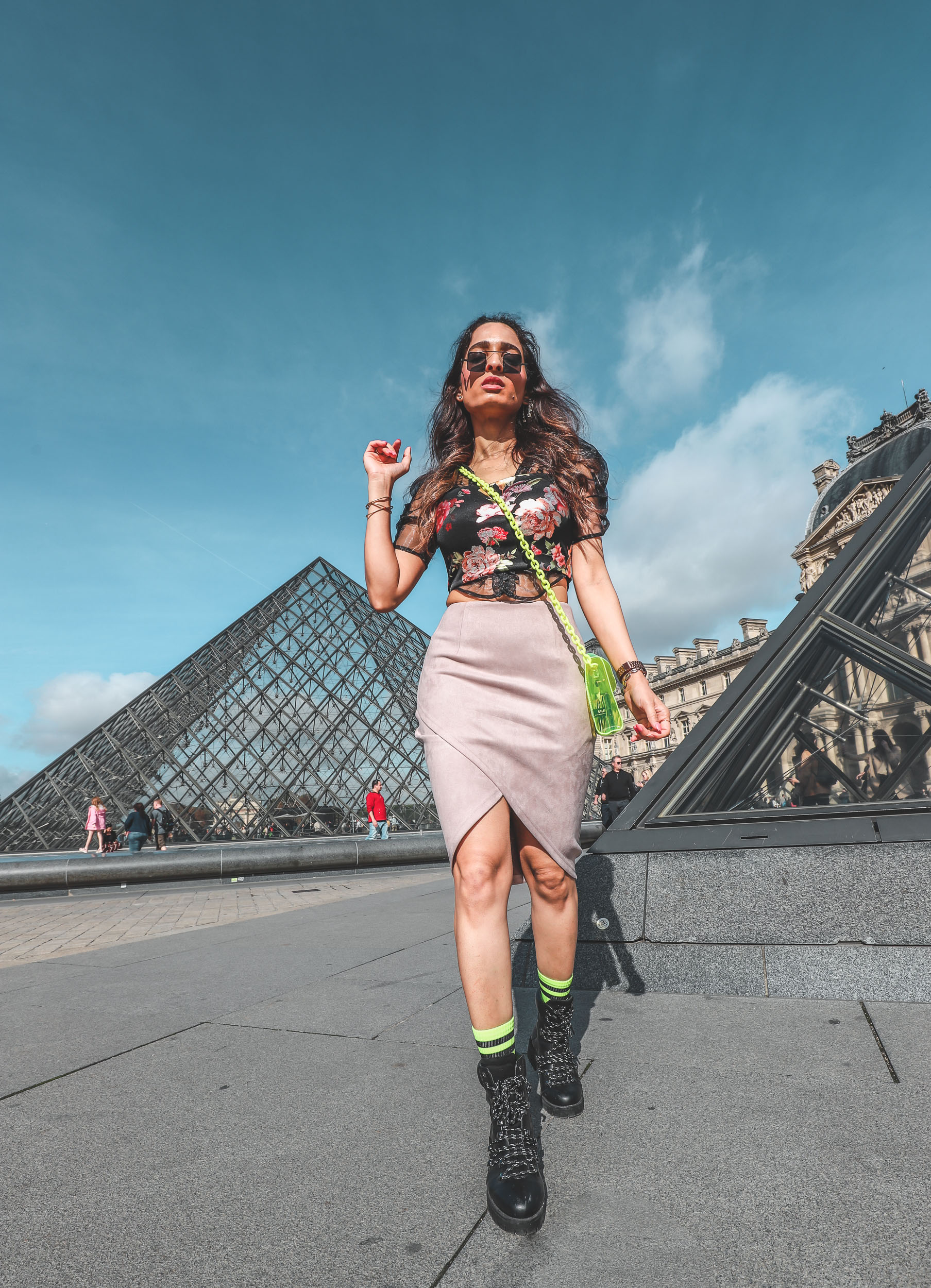 Girl travel blogger and fashion blogger wearing nude pencil skirt with floral crop top and neon purse with neon socks and black hiking boots standing in front of the pyramid at the Louvre museum in Paris for Paris travel guide