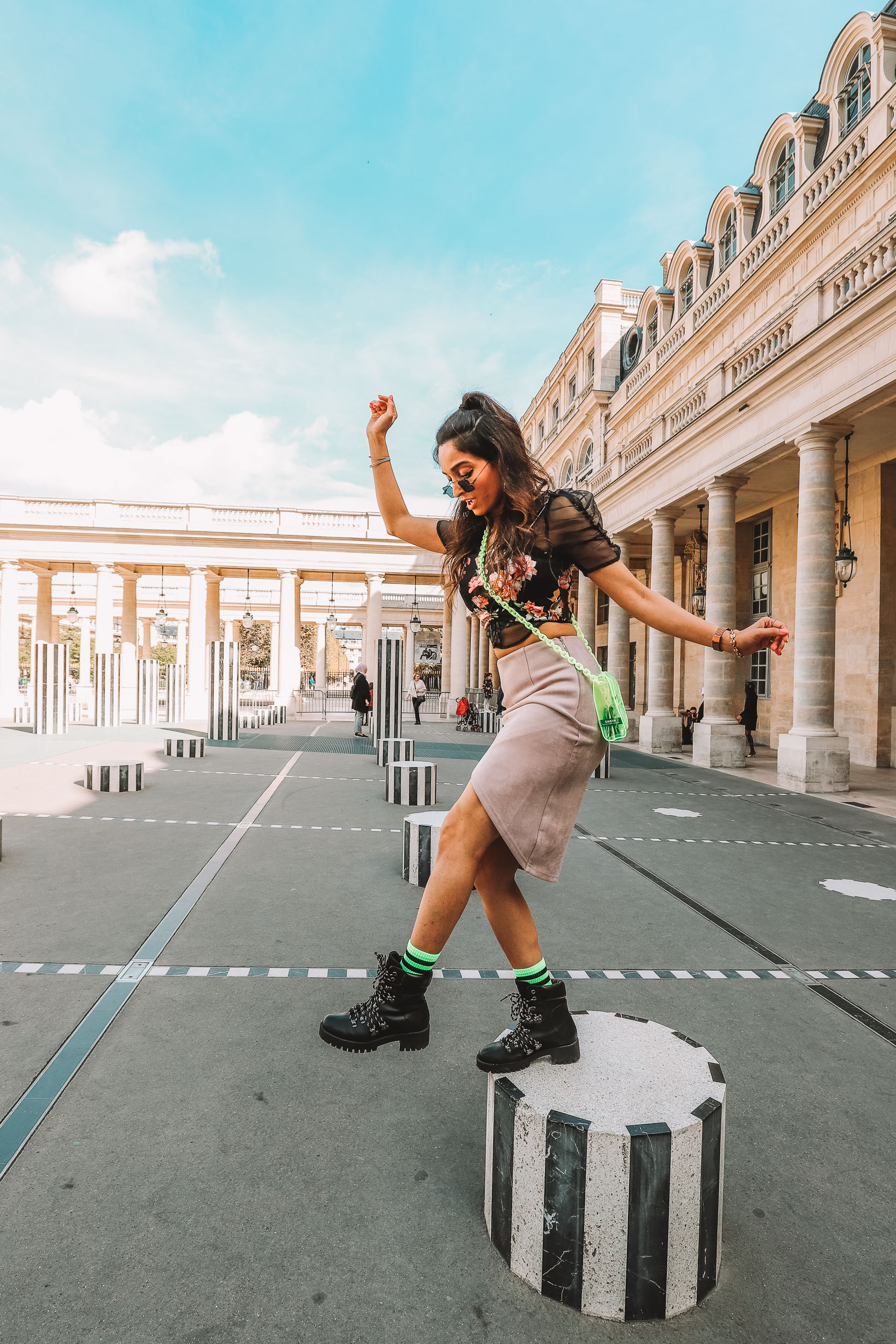 Girl travel blogger and fashion blogger wearing nude pencil skirt with floral crop top and neon purse with neon socks and black hiking boots standing at the Domaine National du Palais-Royal in Paris for Paris travel guide