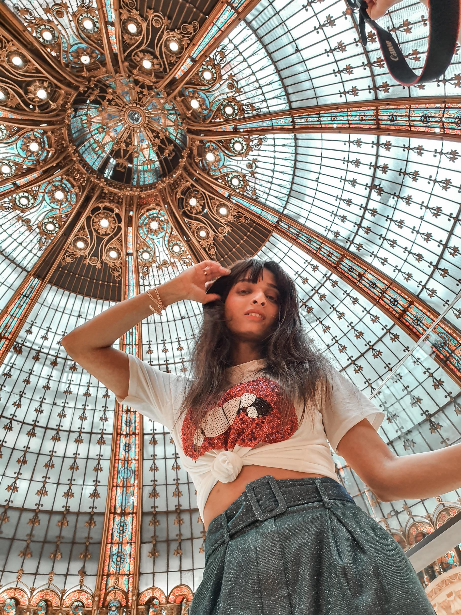 Girl travel blogger and fashion blogger wearing white graphic tee with shimmery blue pants standing at the Galeries Lafayette  in Paris for Paris travel guide
