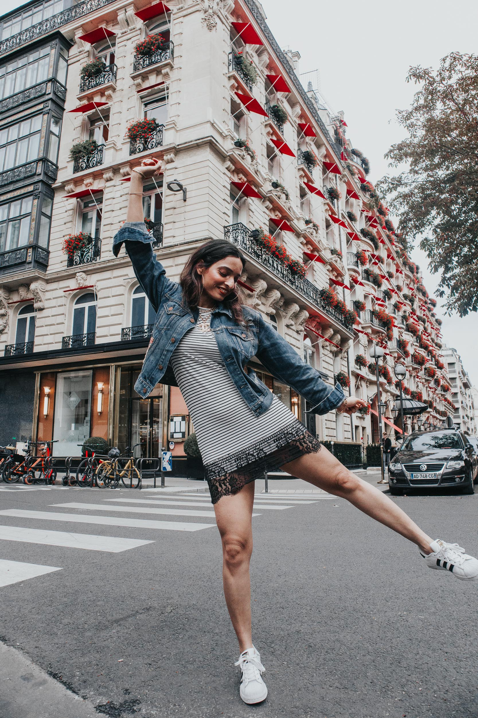 Girl travel blogger and fashion blogger wearing stripe dress and ralph lauren denim jacket and white sneakers, standing on the street in Paris in front of Plaza Athenee for Paris travel guide