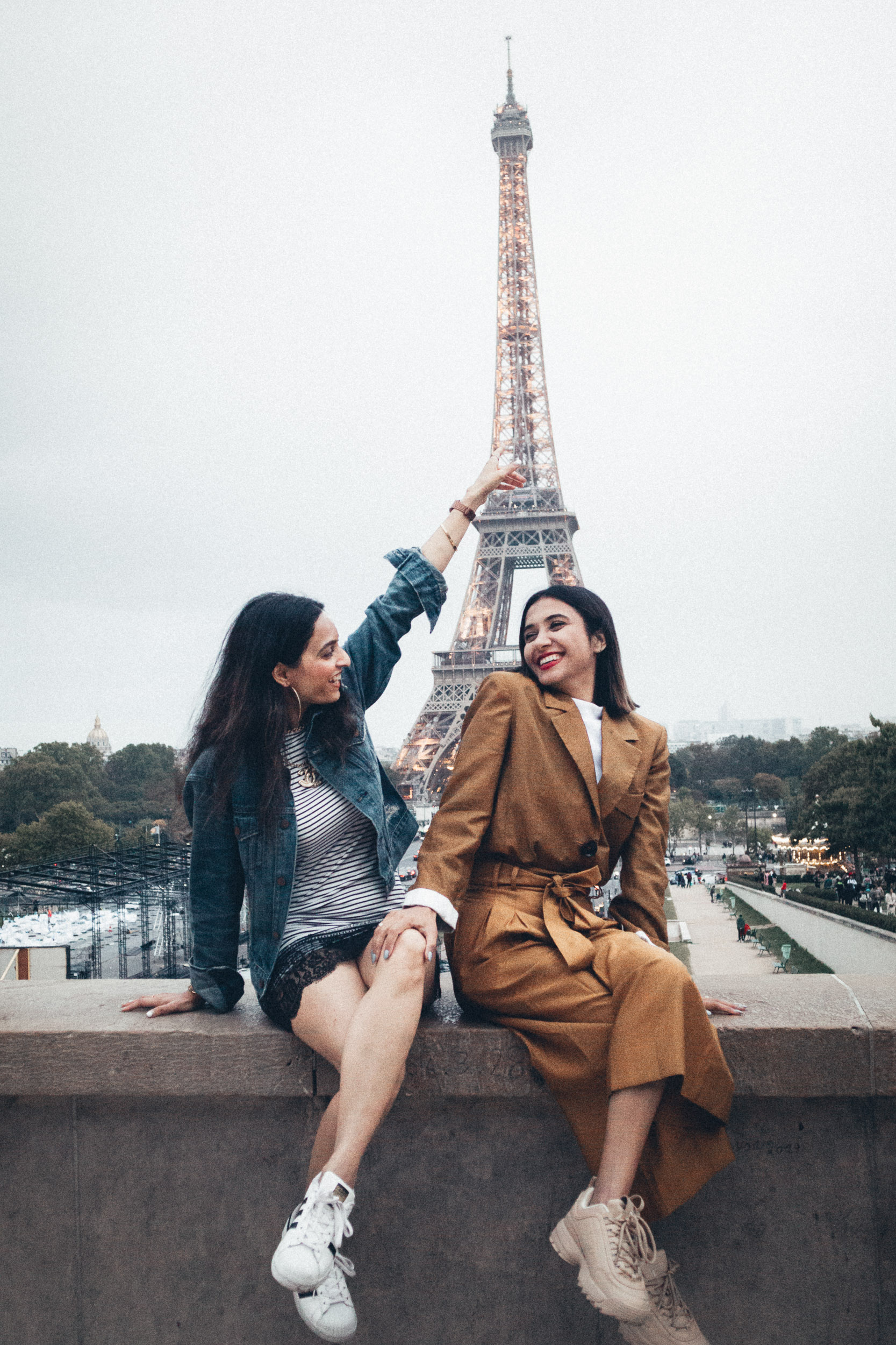 Young Girl friends travel bloggers and fashion bloggers sitting in front of the Eiffel Tower in Paris for Paris travel guide