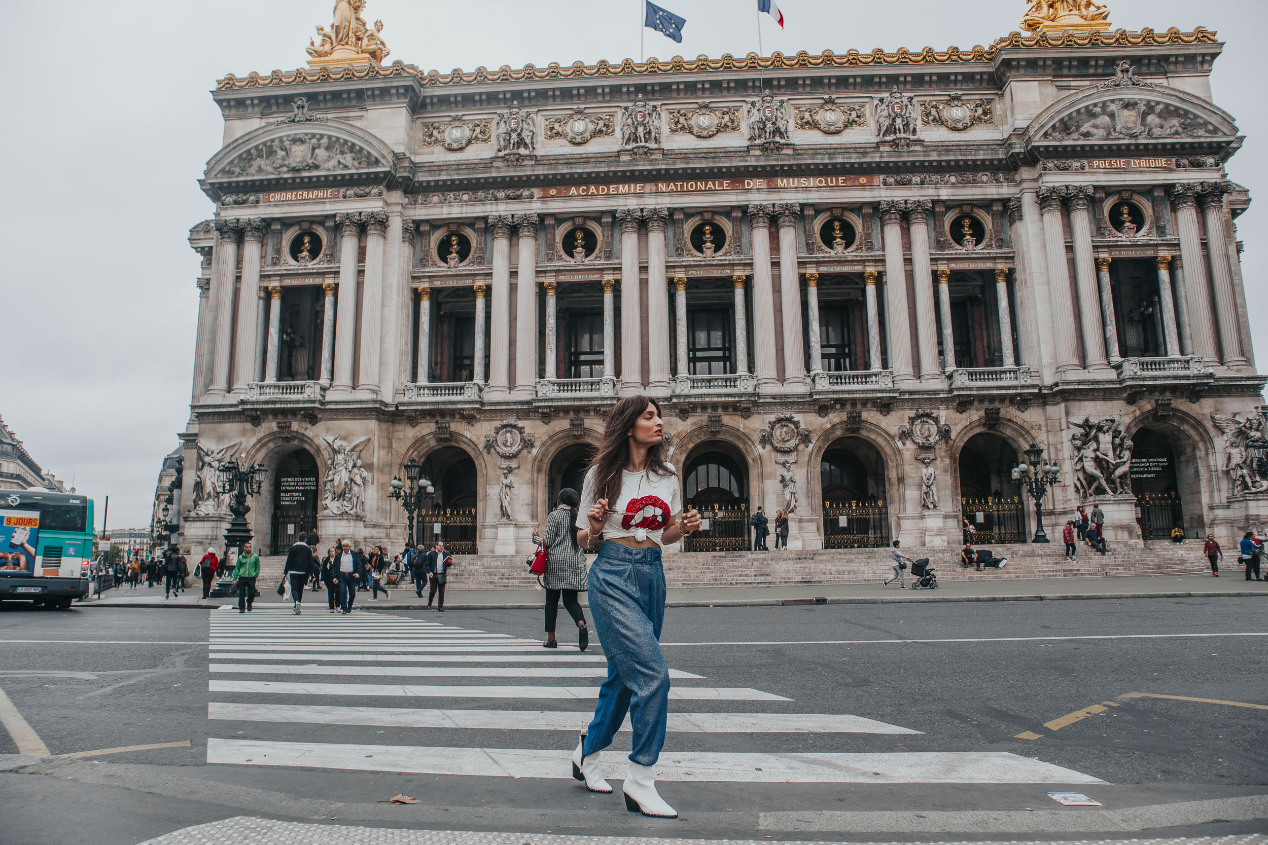 Girl fashion blogger and travel blogger crossing the road near the Palais Garnier at in Paris for Paris travel guide