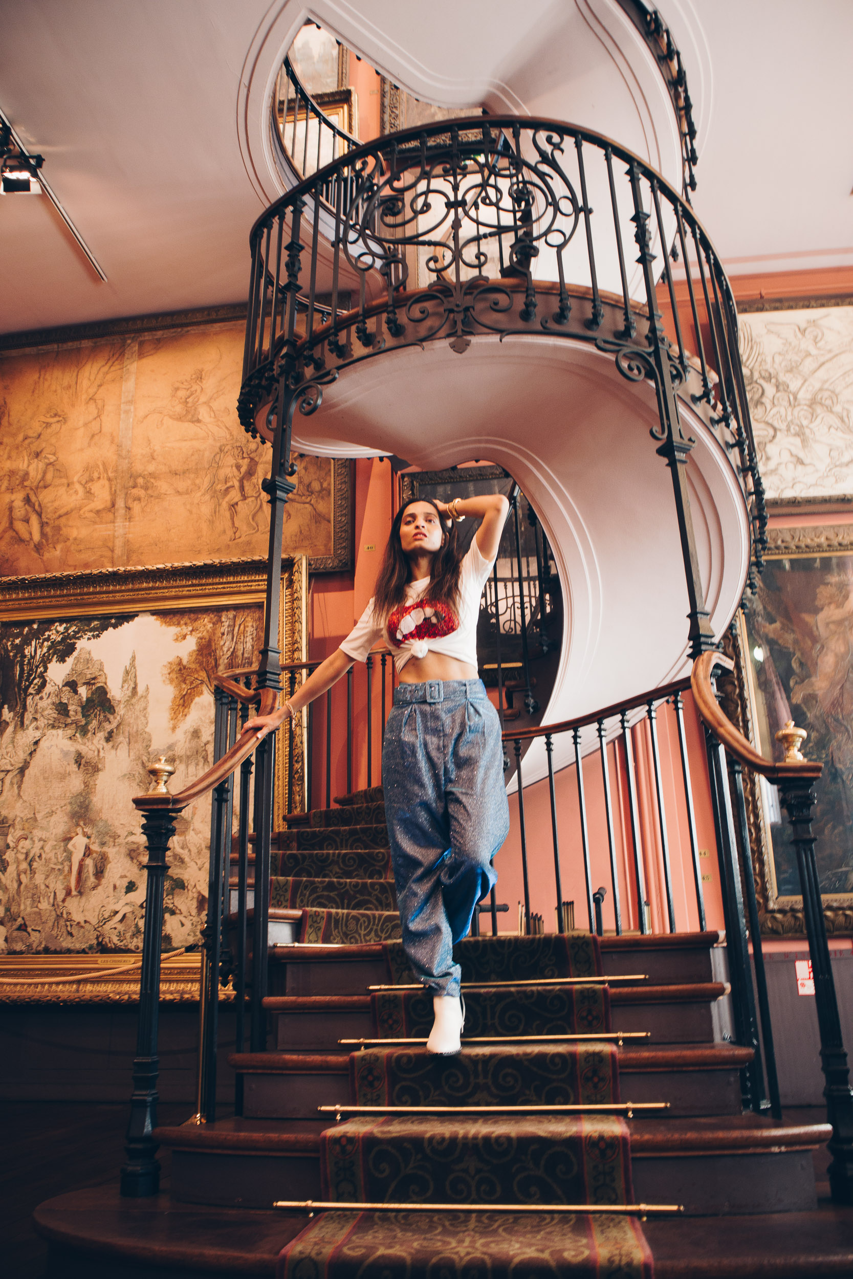 Girl travel blogger and fashion blogger wearing white graphic tee with shimmery blue pants and white boots sitting at the staircase of Musée national Gustave Moreau in Paris for Paris travel guide