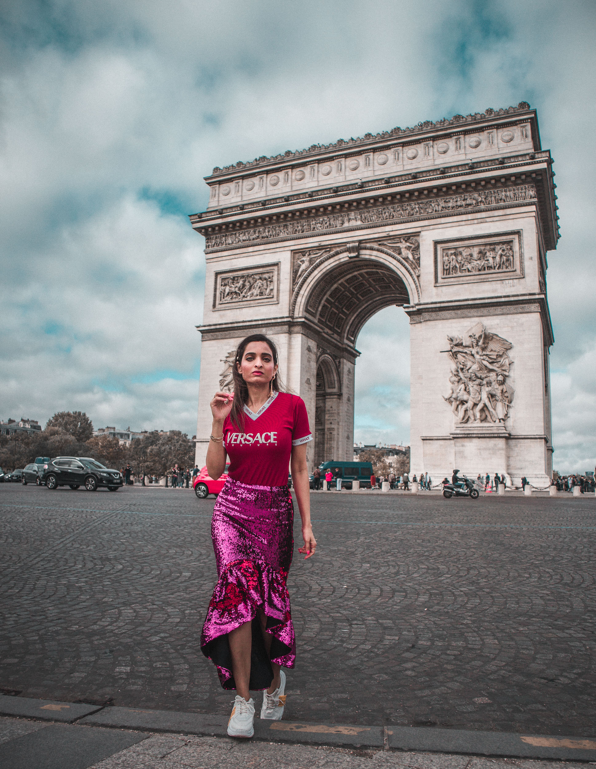 Girl travel blogger and fashion blogger wearing pink sequin Rachel Gilbert skirt with red versace tee shirt standing in front of the Arc de Triomphe in Paris for Paris travel guide
