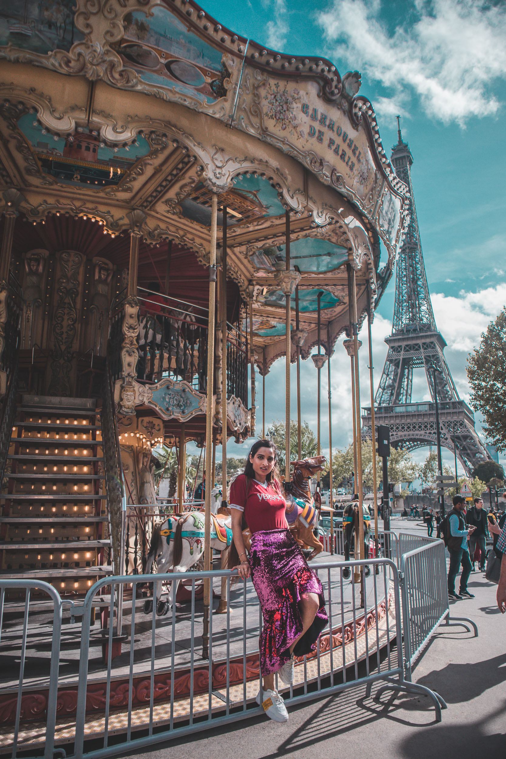 Girl travel blogger and fashion blogger wearing pink sequin Rachel Gilbert skirt standing in front of the carousel and Eiffel tower in Paris for Paris travel guide