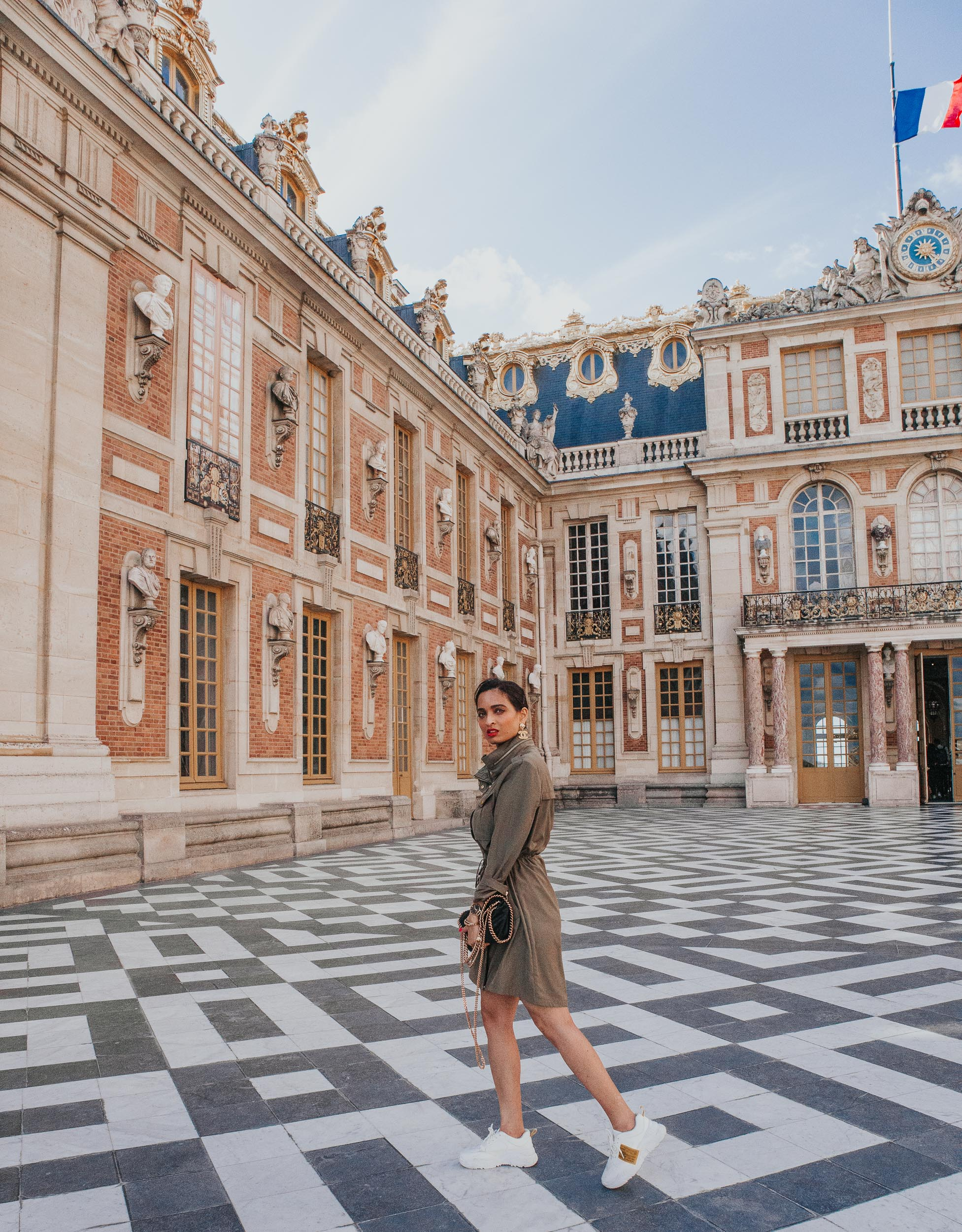 Girl travel blogger and fashion blogger wearing olive green trench dress by Badgeley Mischka with gold accessories standing at the Palace of Versailles in France for Paris travel guide