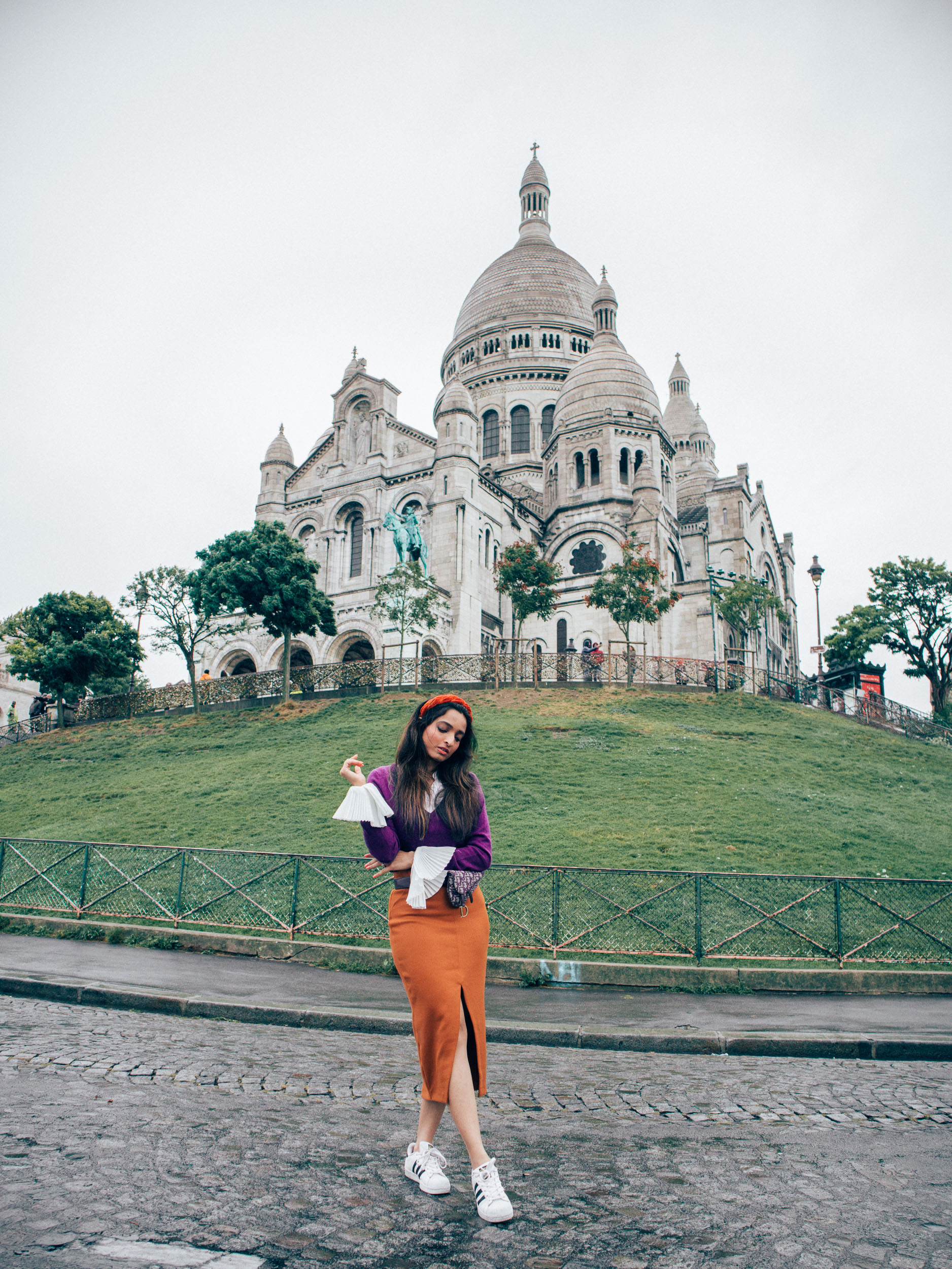 Girl travel blogger and fashion blogger wearing purple sweater with white exaggerated cuffs and rust orange skirt with headband and dior saddle waist bag at Sacré-Cœur in Montmartre in Paris for Paris travel guide
