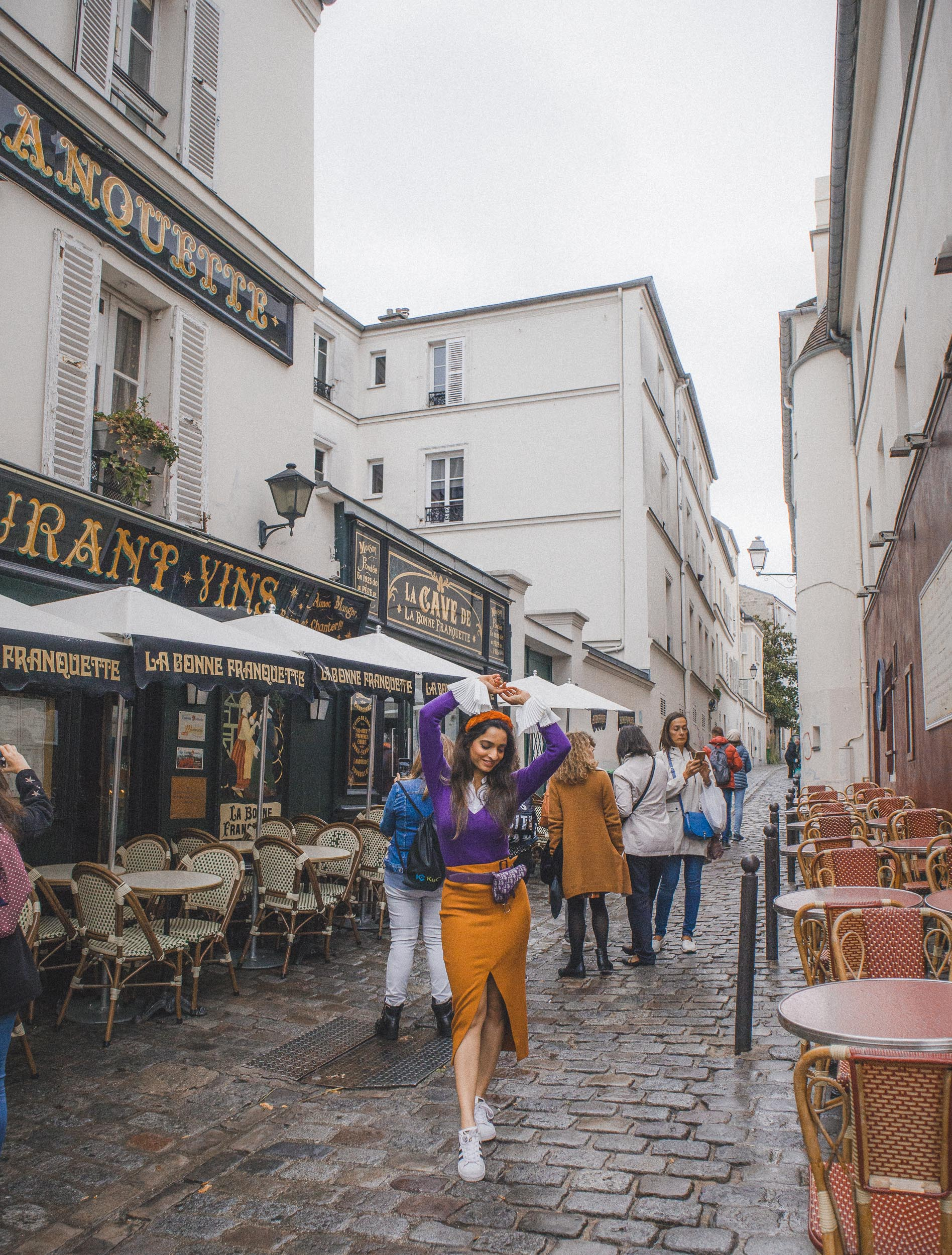 Girl travel blogger and fashion blogger wearing purple sweater with white exaggerated cuffs and rust orange skirt with headband and dior saddle waist bag at Montmartre in Paris for Paris travel guide