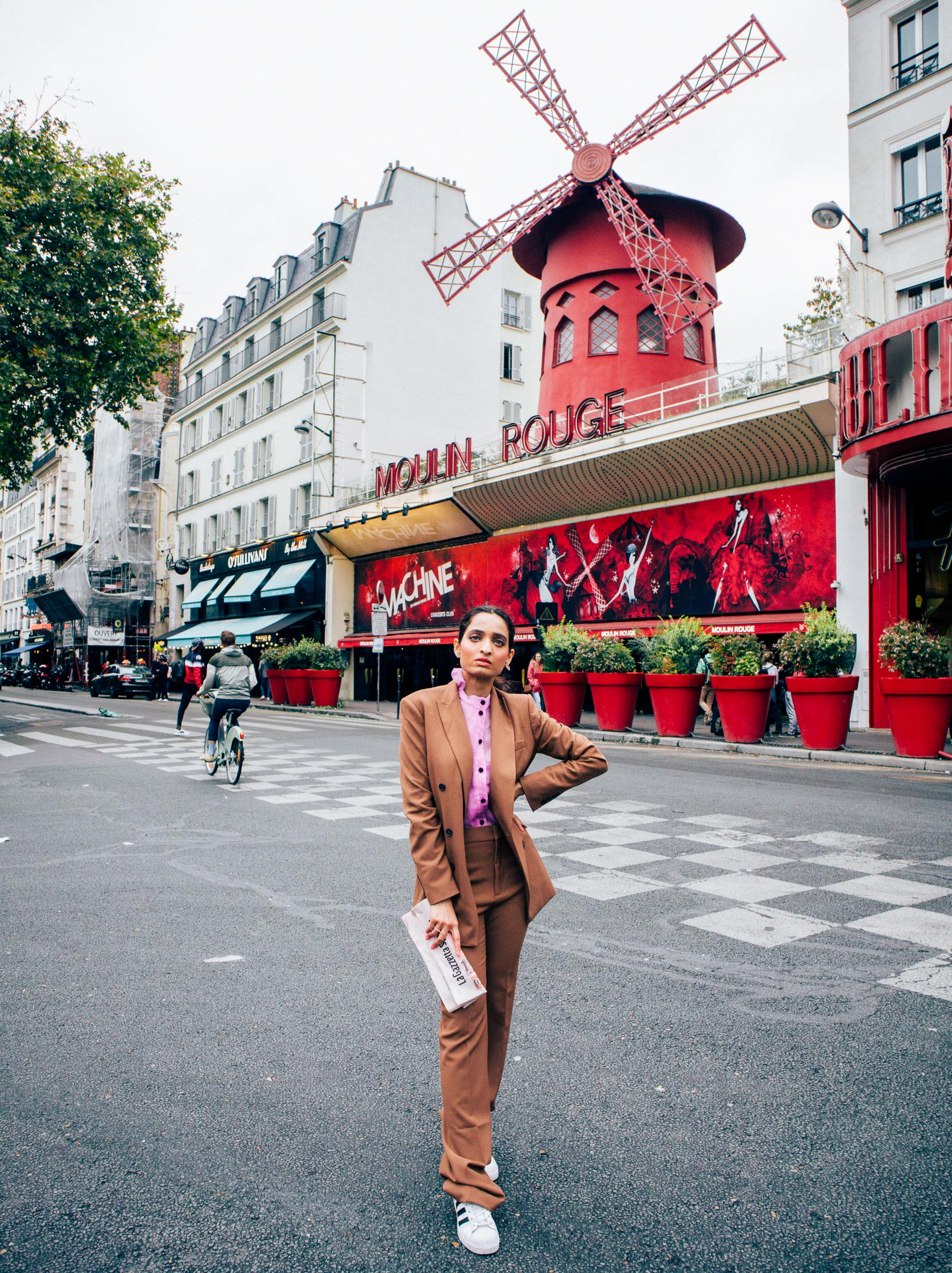 Girl travel blogger and fashion blogger wearing camel coloured suit with lavender shirt standing in front of the Moulin Rogue in Paris for Paris travel guide
