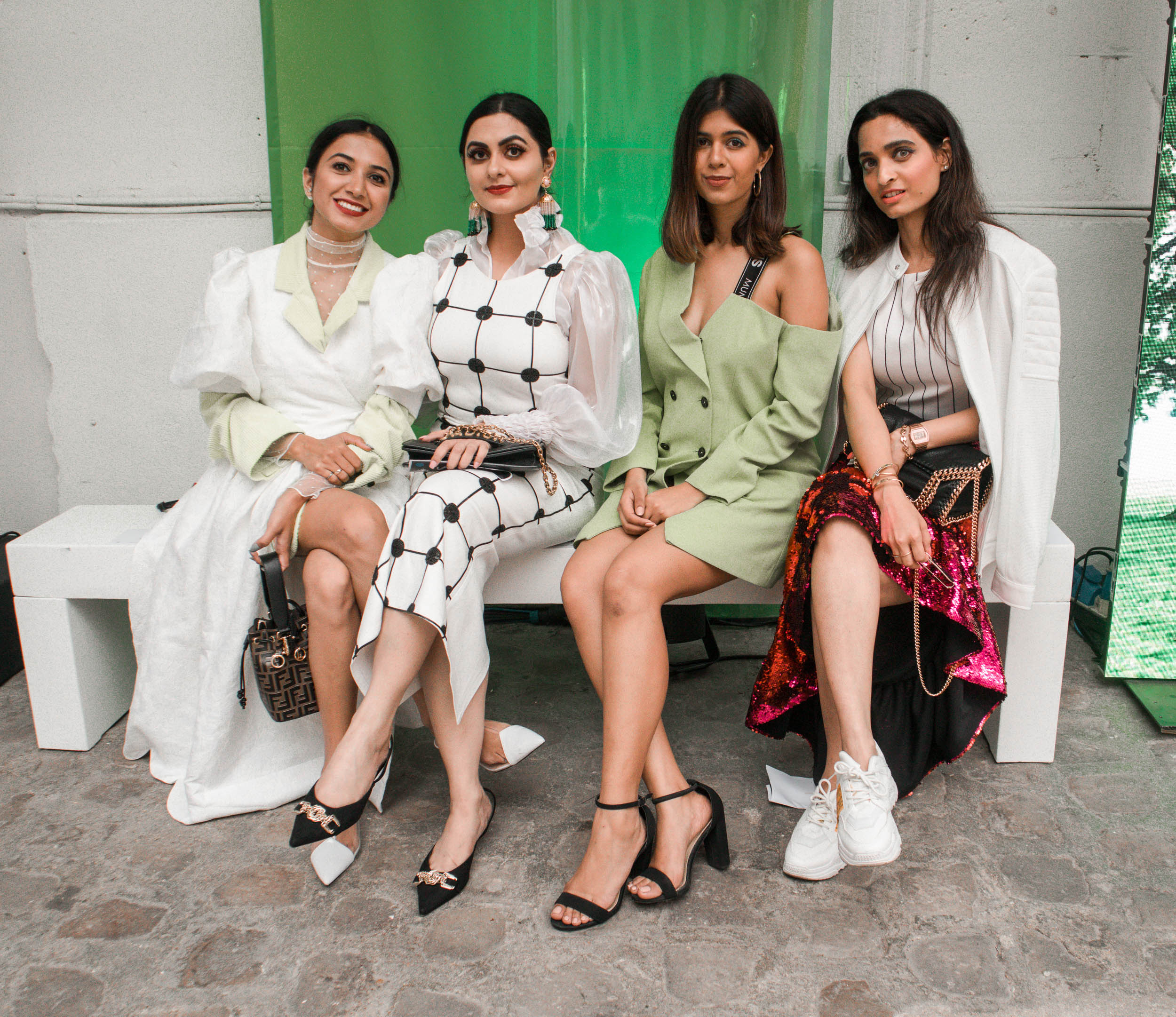 four Girl fashion bloggers sitting together on a bench at the Paris Fashion Week for Tatras show in Paris for Paris travel guide