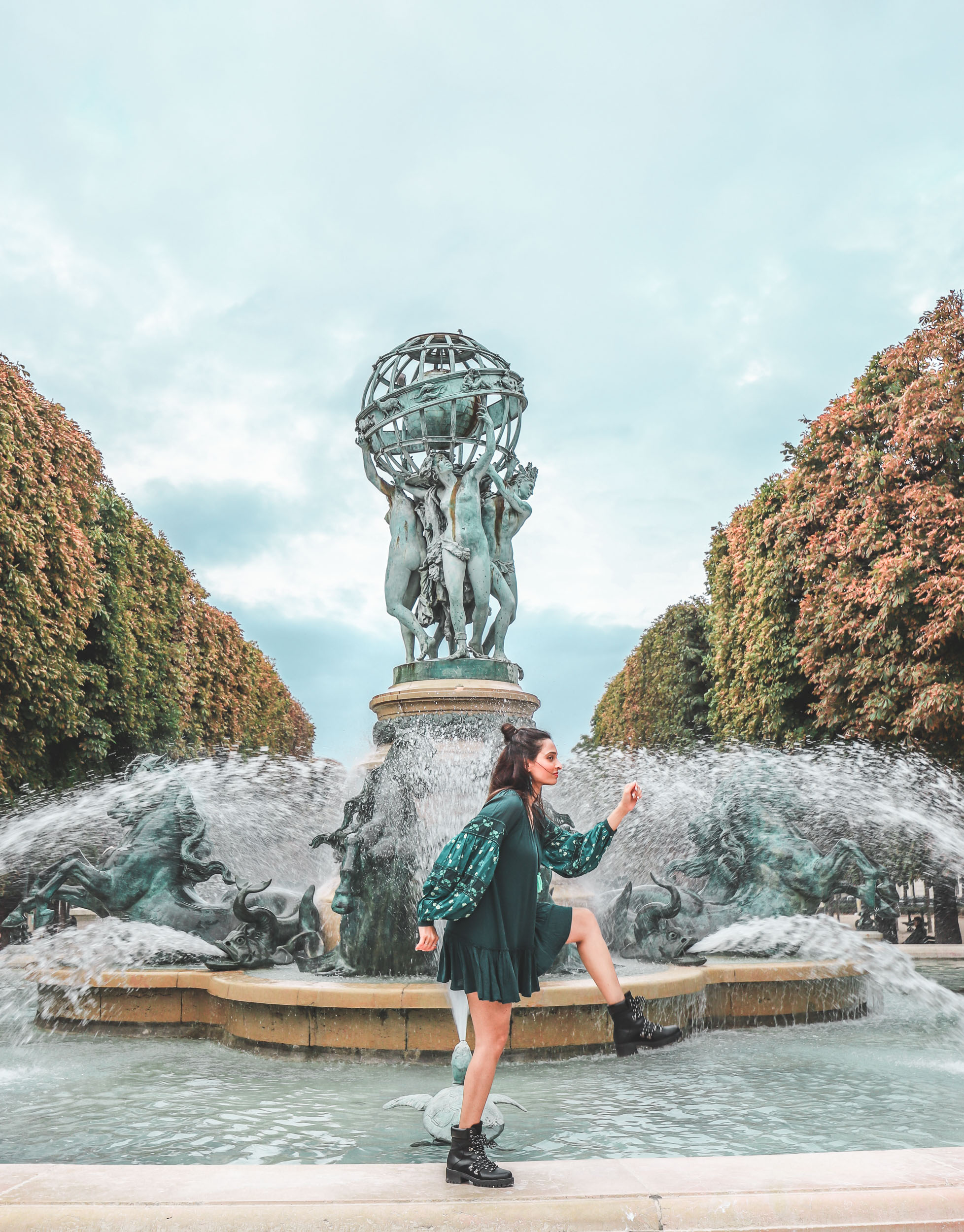 Girl travel blogger and fashion blogger wearing blue flared short dress and bell sleeves with black hiking boots at the fountain at Luxembourg Gardens in Paris for Paris travel guide
