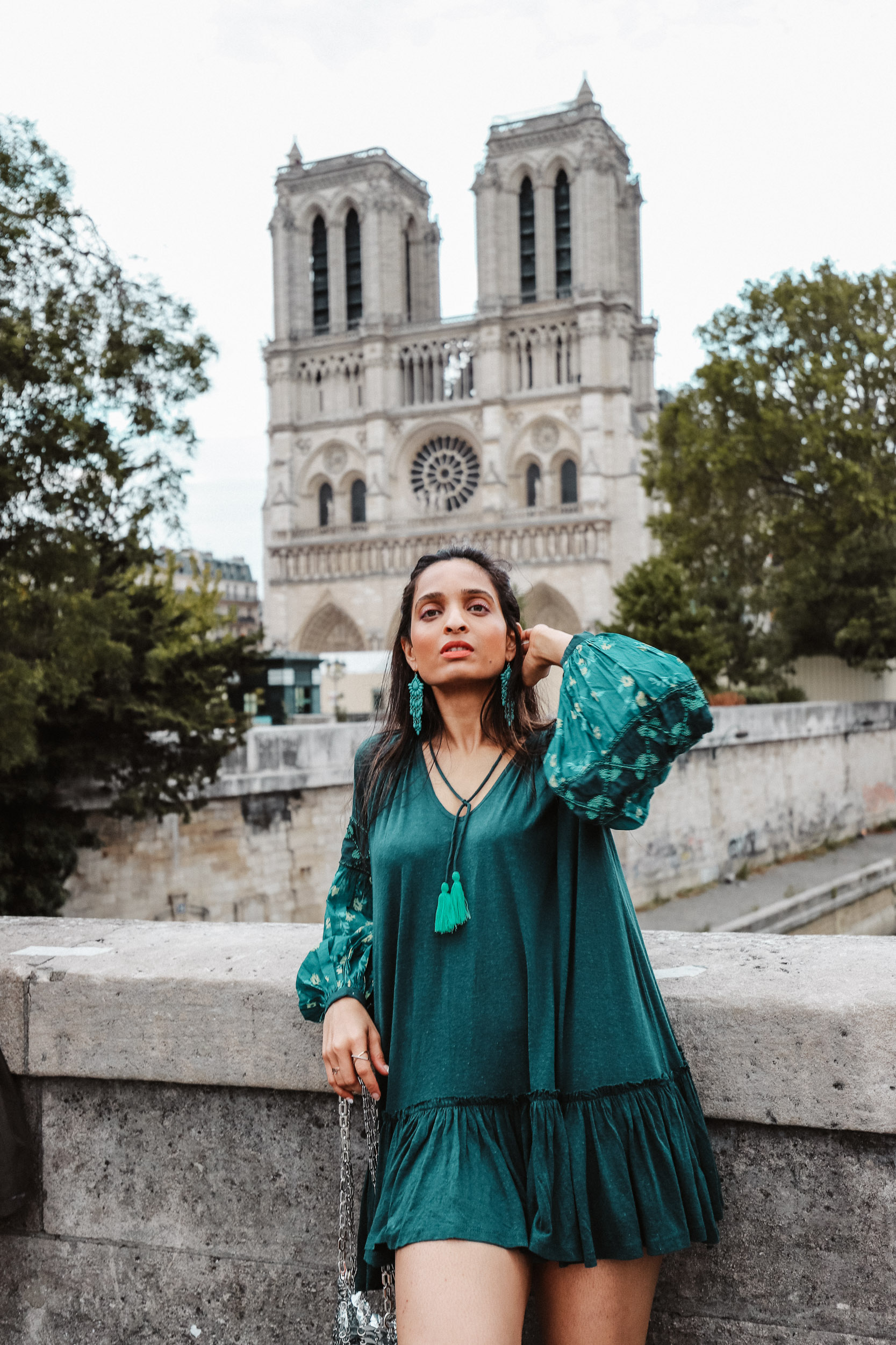 Girl travel blogger and fashion blogger wearing blue flared short dress and bell sleeves at Notre Dame in Paris for Paris travel guide