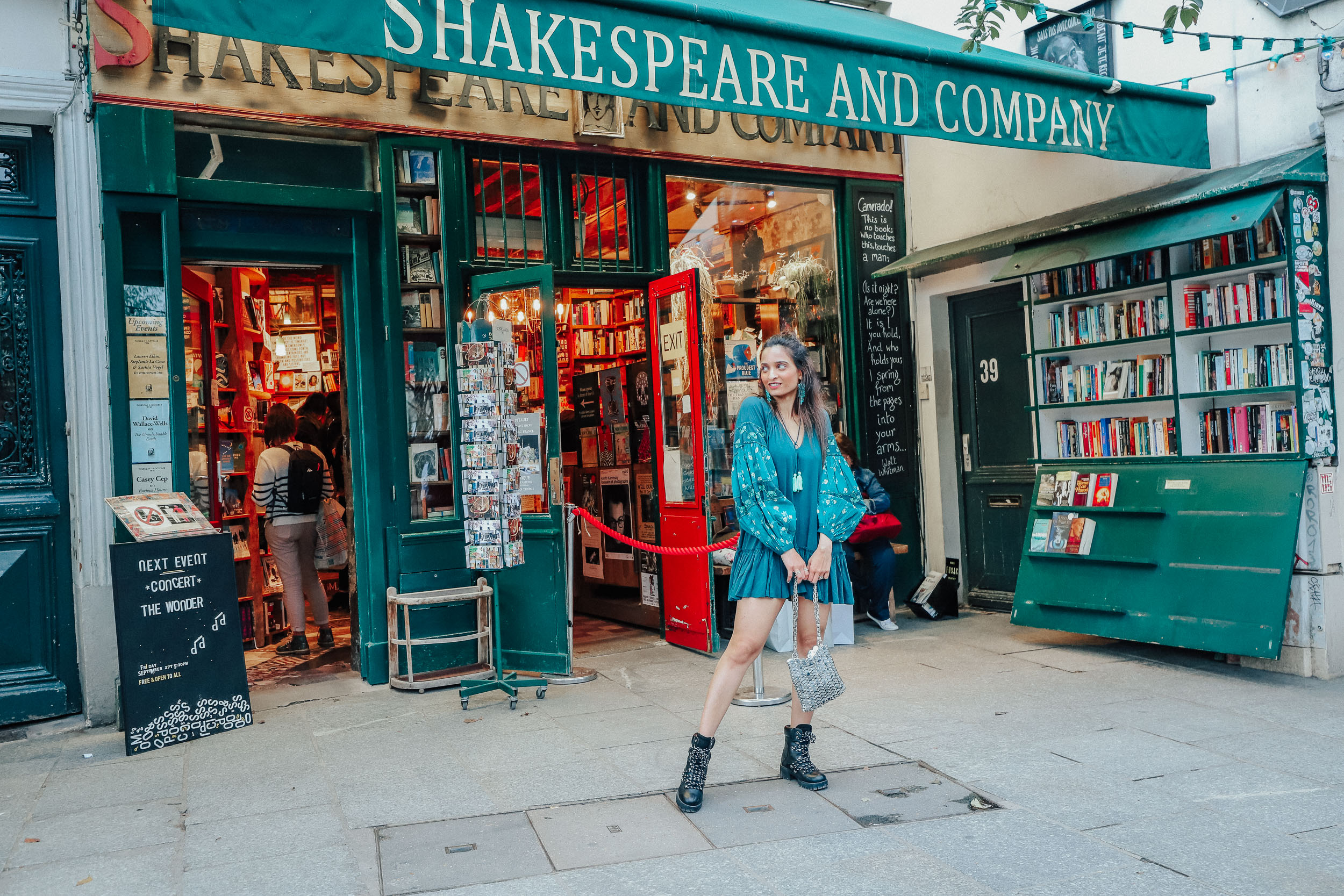 Girl travel blogger and fashion blogger wearing blue flared short dress and bell sleeves at Shakespeare and Company in Paris for Paris travel guide