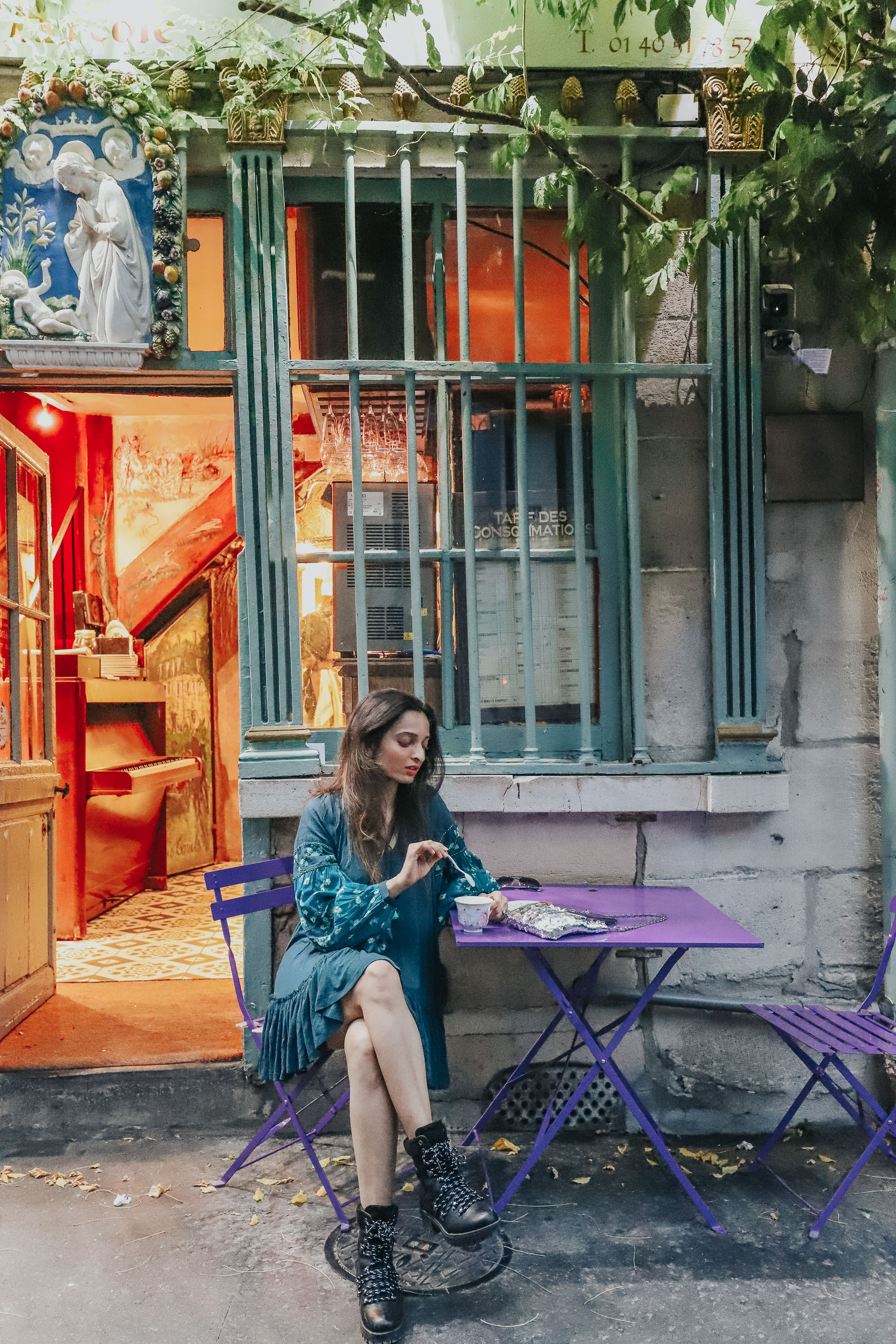 Girl travel blogger and fashion blogger wearing blue flared short dress and bell sleeves at a colourful cafe in Paris for Paris travel guide
