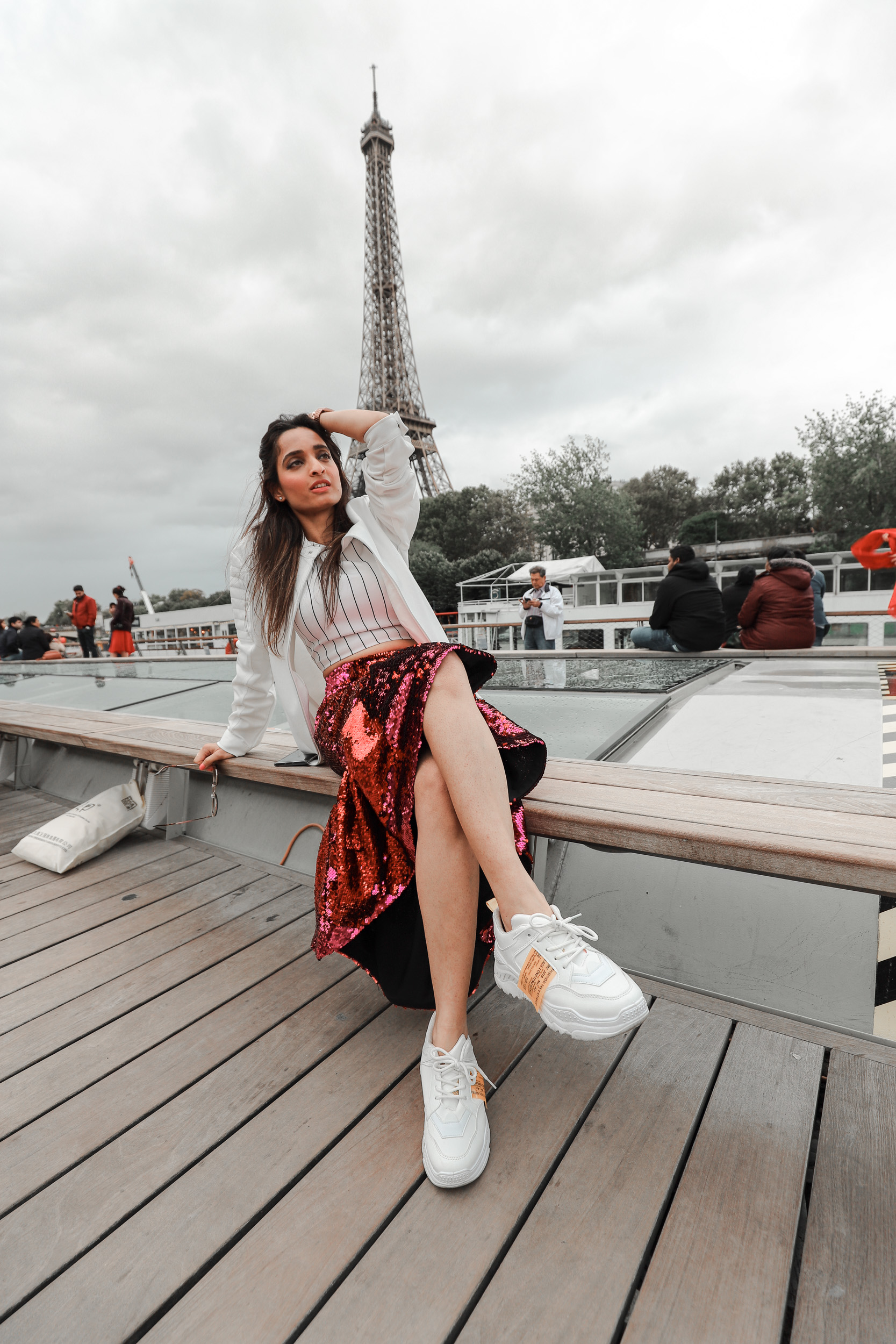 Girl travel blogger and fashion blogger wearing pink sequin skirt with white top and white bomber jacket and white sneakers, sitting in the boat at the Seine river cruise with Eiffel tower in the back in Paris for Paris travel guide