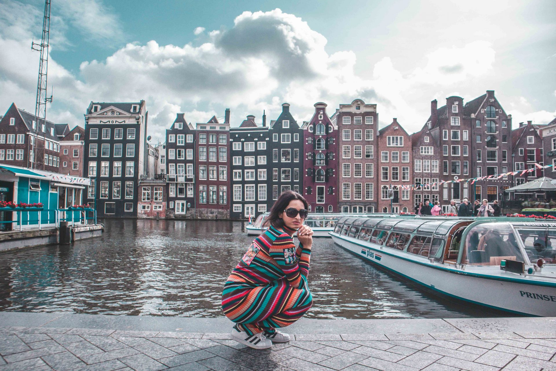girl fashion blogger and travel blogger wearing striped full length bodycon dress by Jeremy Scott and siiting in front of the colourful houses in Amsterdam, Holland
