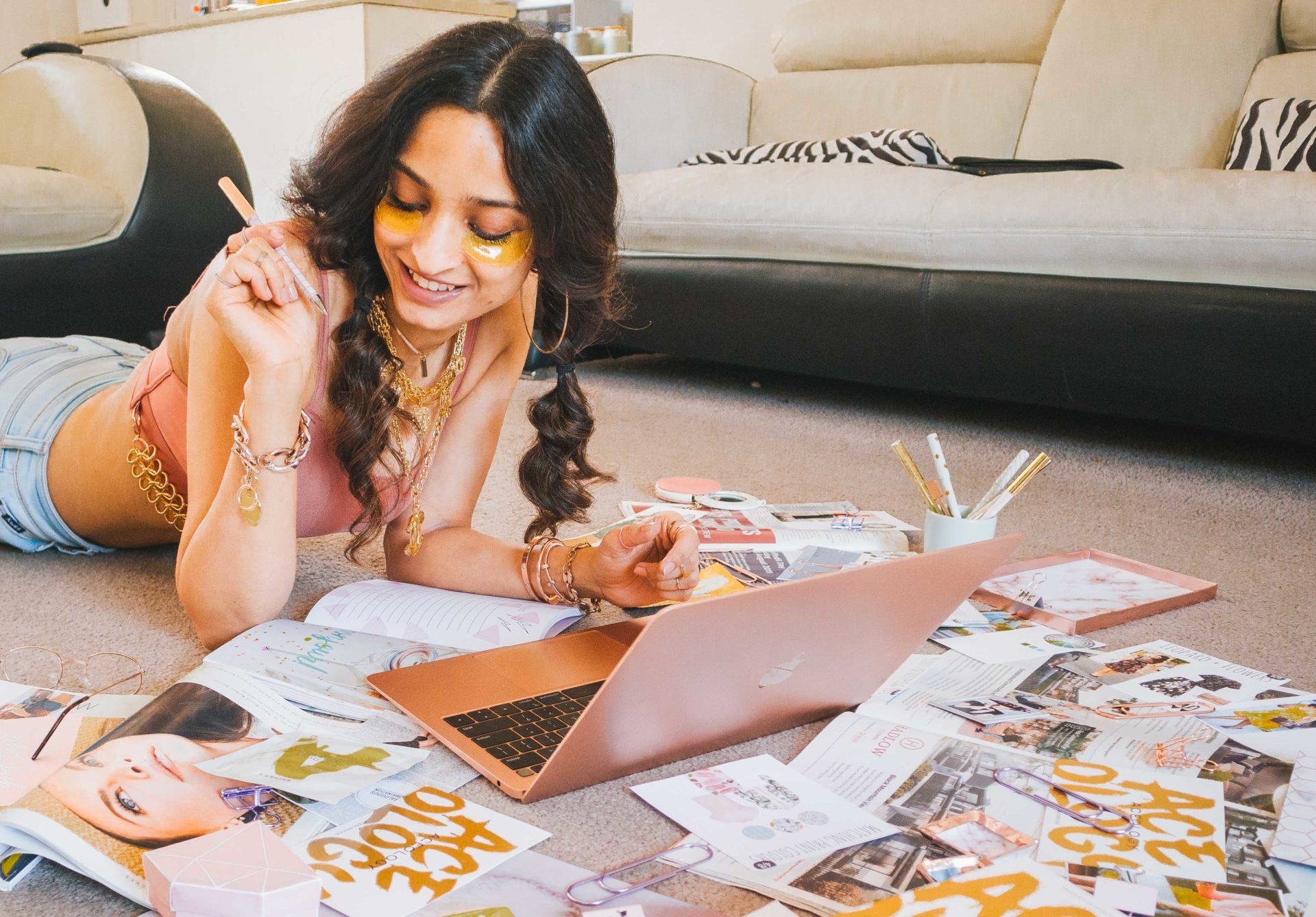 girl lying on floor carpet at home with pictures and laptop