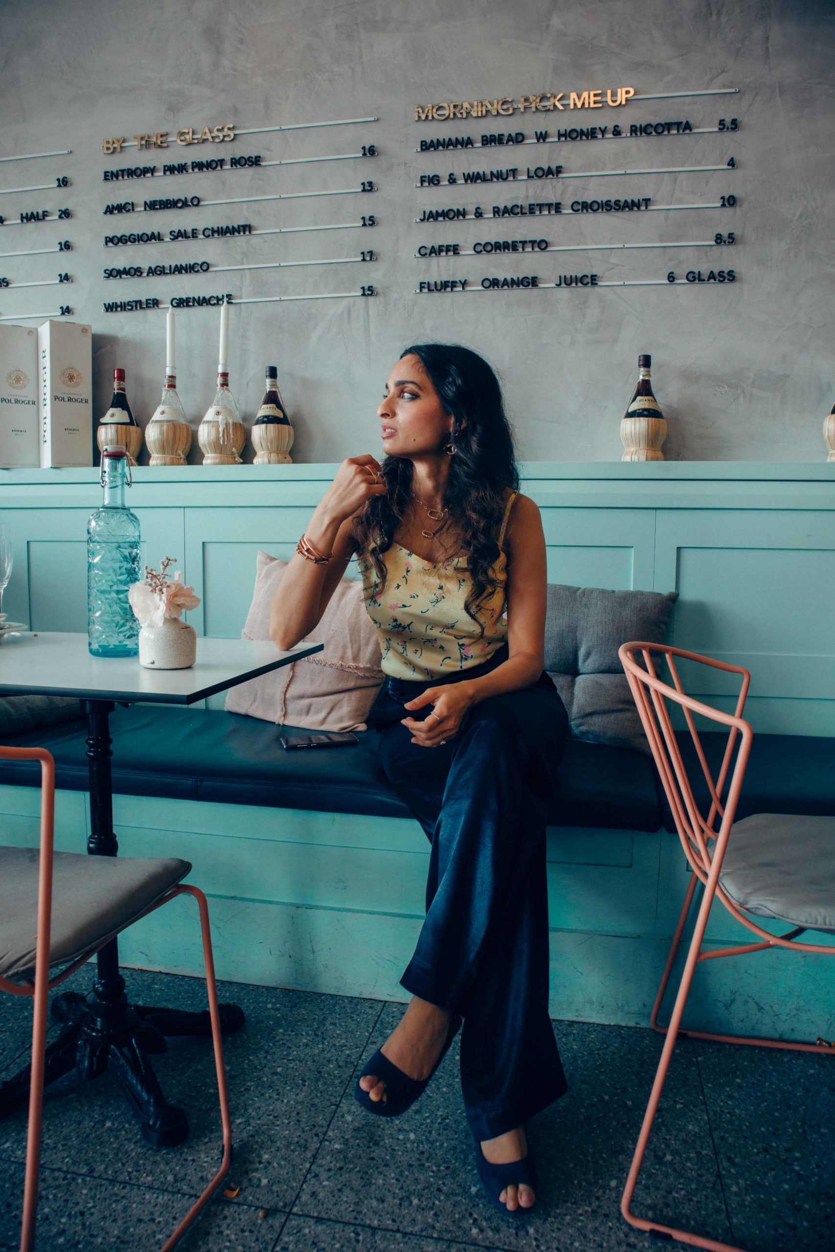 girl fashion blogger sitting in a blue and grey aesthetic cafe wearing satin yellow camisole top and satin blue palzzo pants