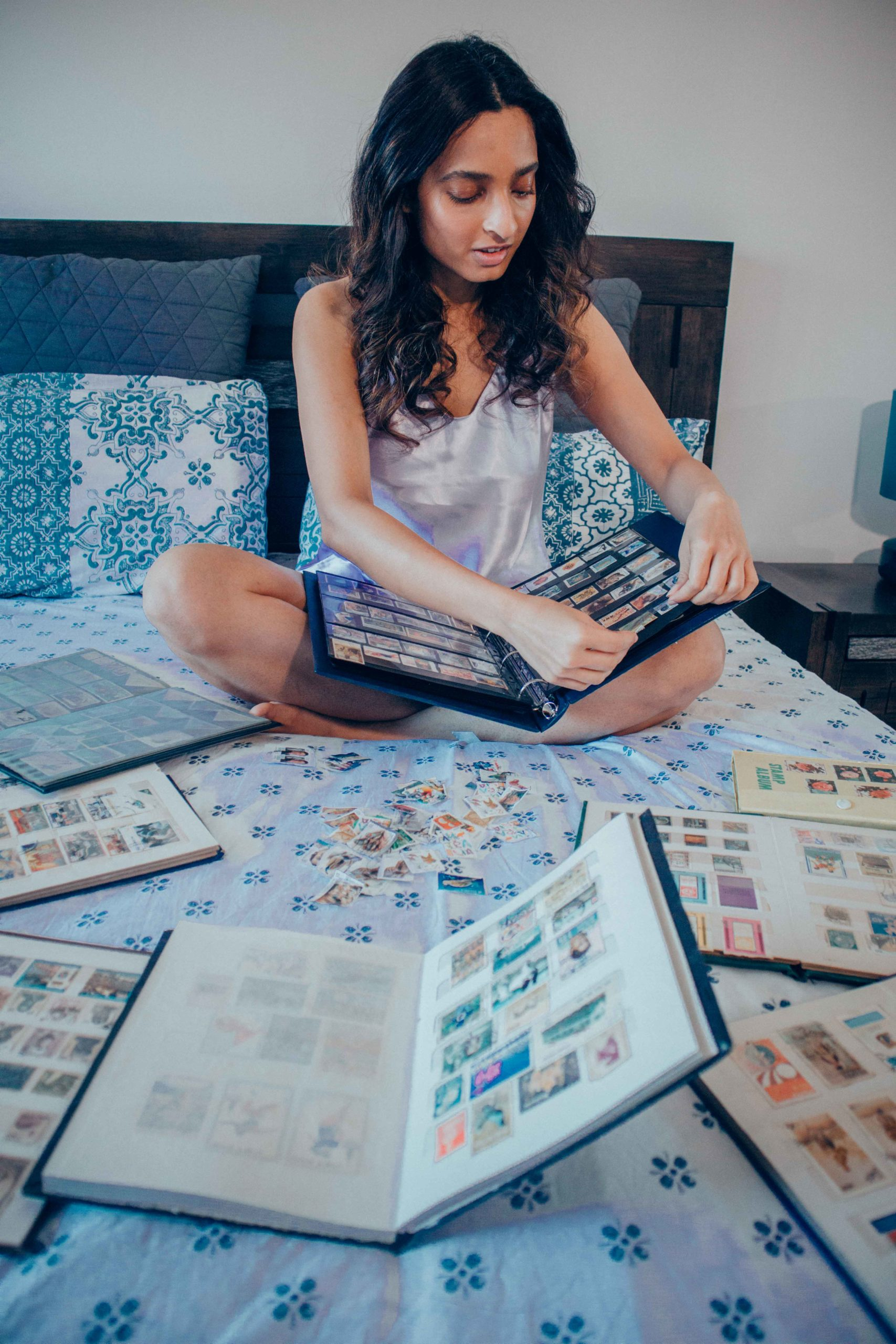 girl sitting on bed wearing lavender silk camisole pyjamas going through her stamp collection